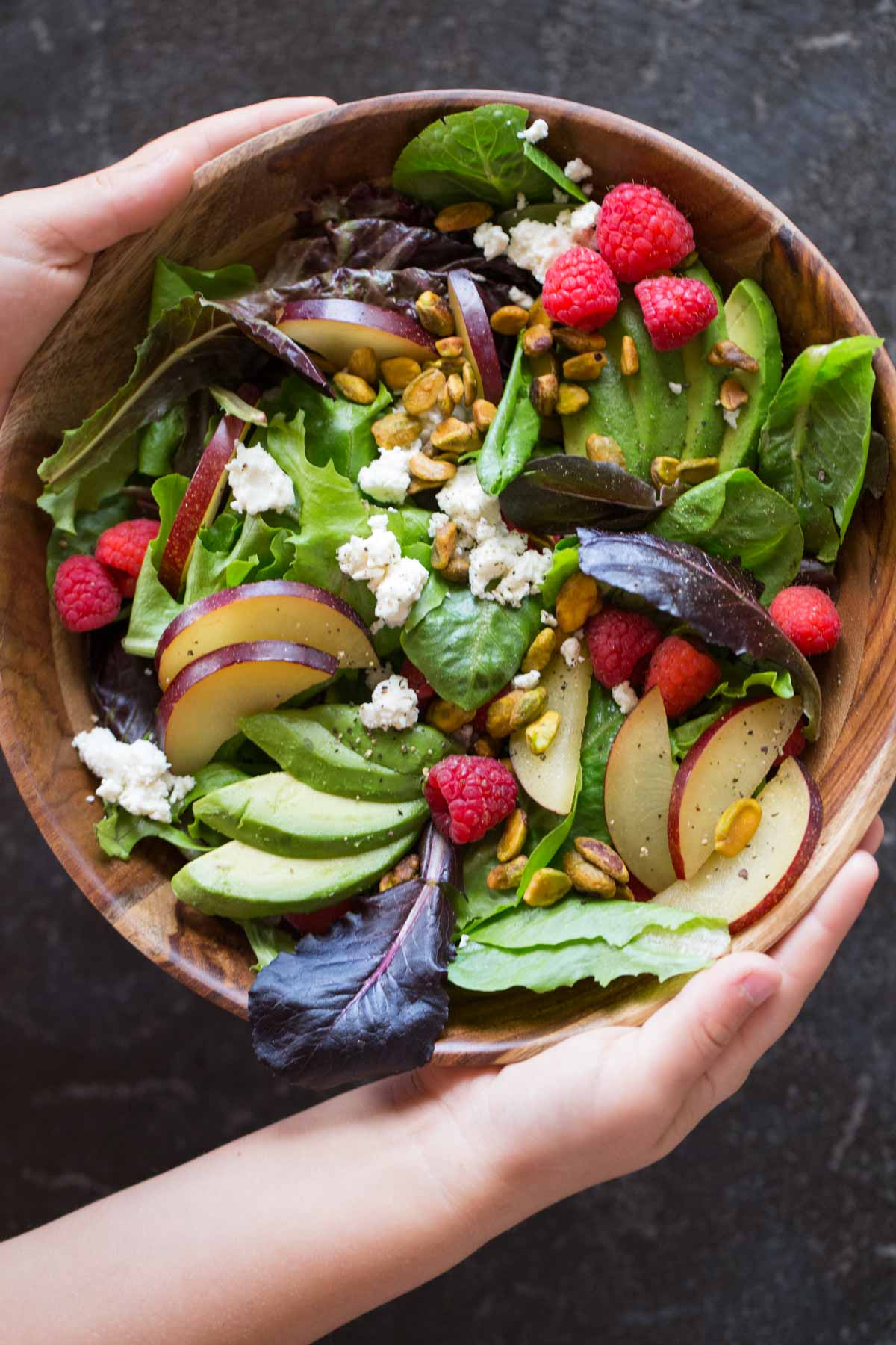 Summer Fruited Salad with Goat Cheese and Pistachios in a wood bowl.