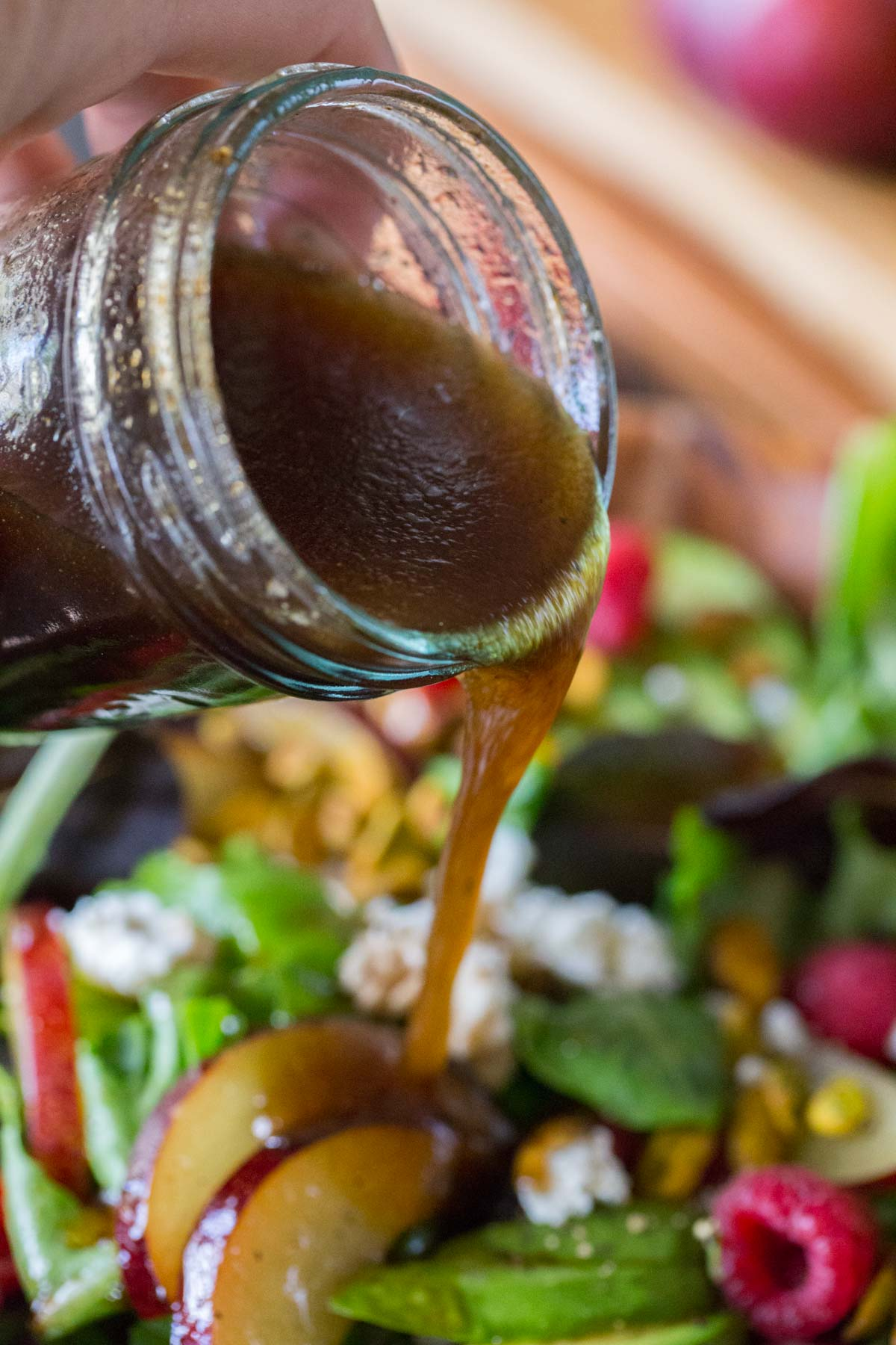 A glass jar of homemade balsamic vinaigrette being poured on top of the Summer Fruited Salad with Goat Cheese and Pistachios.