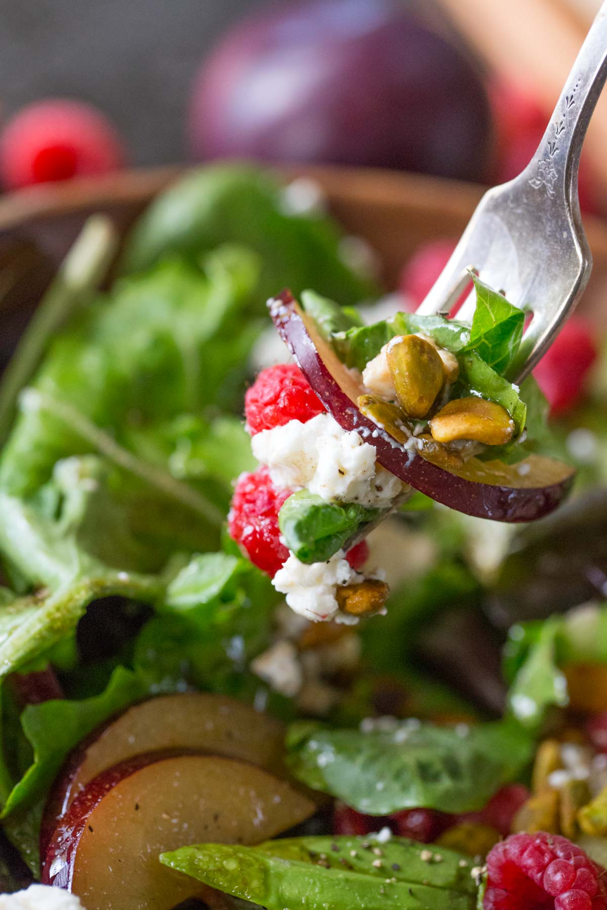 A fork full of Summer Fruited Salad with Goat Cheese and Pistachios held over the bowl of salad.