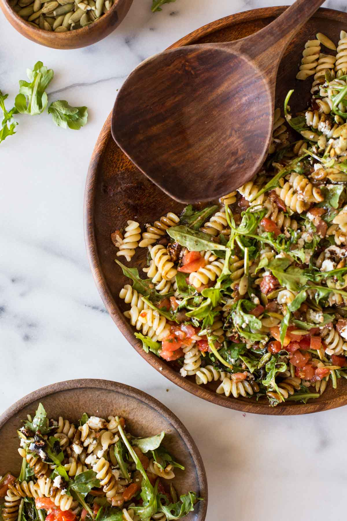 Bruschetta Pasta Salad on a wood serving platter with a wooden spoon, sitting next to a plate of Bruschetta Pasta Salad and a small bowl of pepitas.