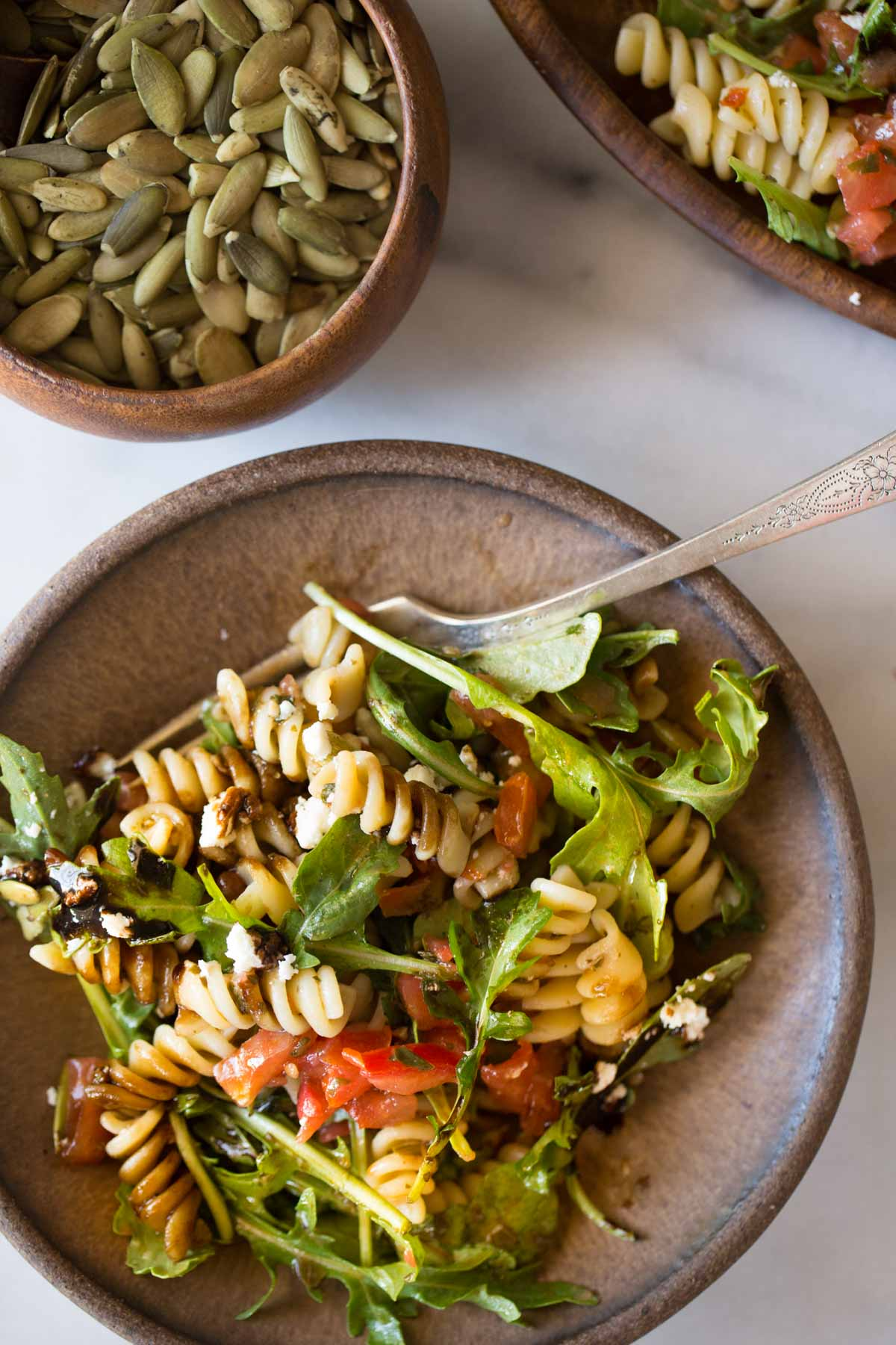 Bruschetta Pasta Salad on a plate with a fork, next to a small bowl of pepitas.