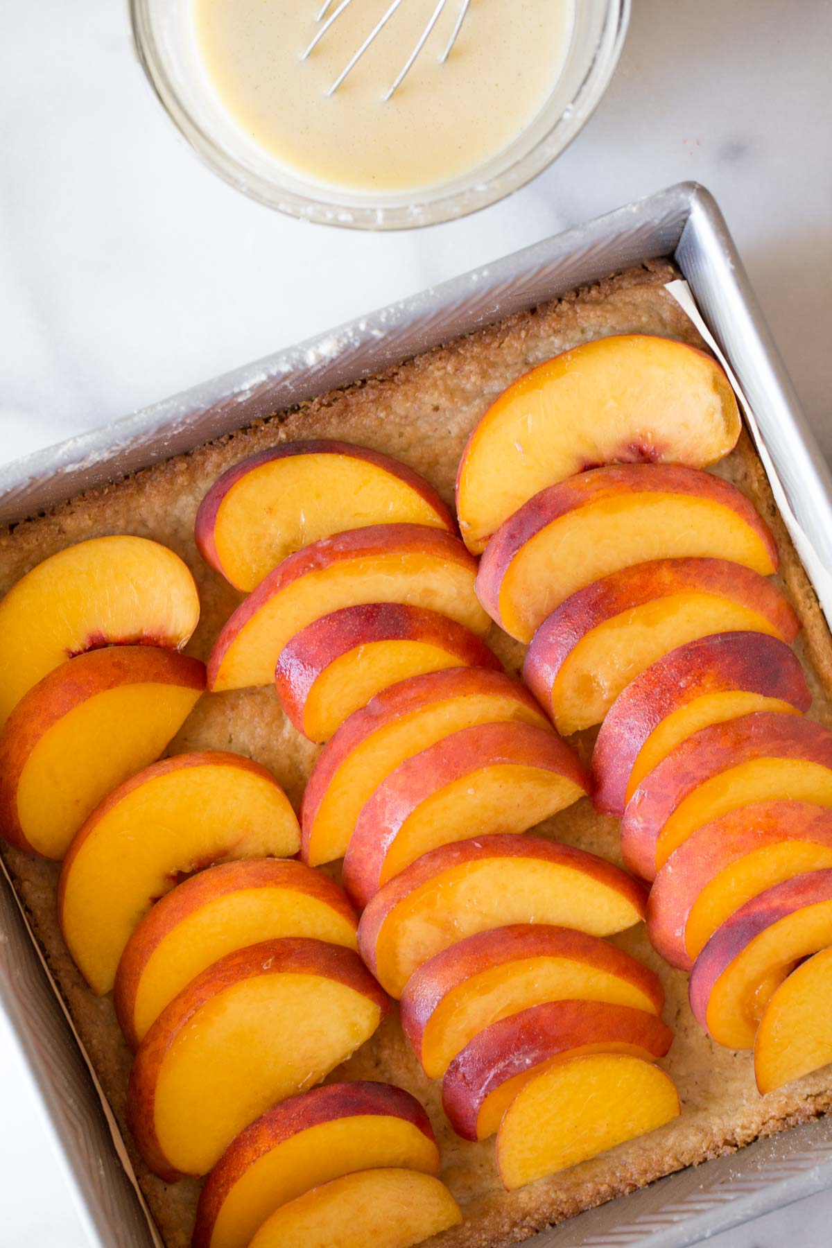 A baking dish with the fresh sliced peaches placed on top of the almond shortbread crust, with a bowl of creamy vanilla custard next to it.