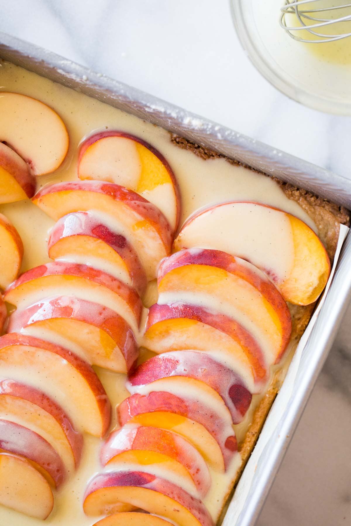 Peaches and Cream Shortbread Bars assembled in a baking dish prior to baking.