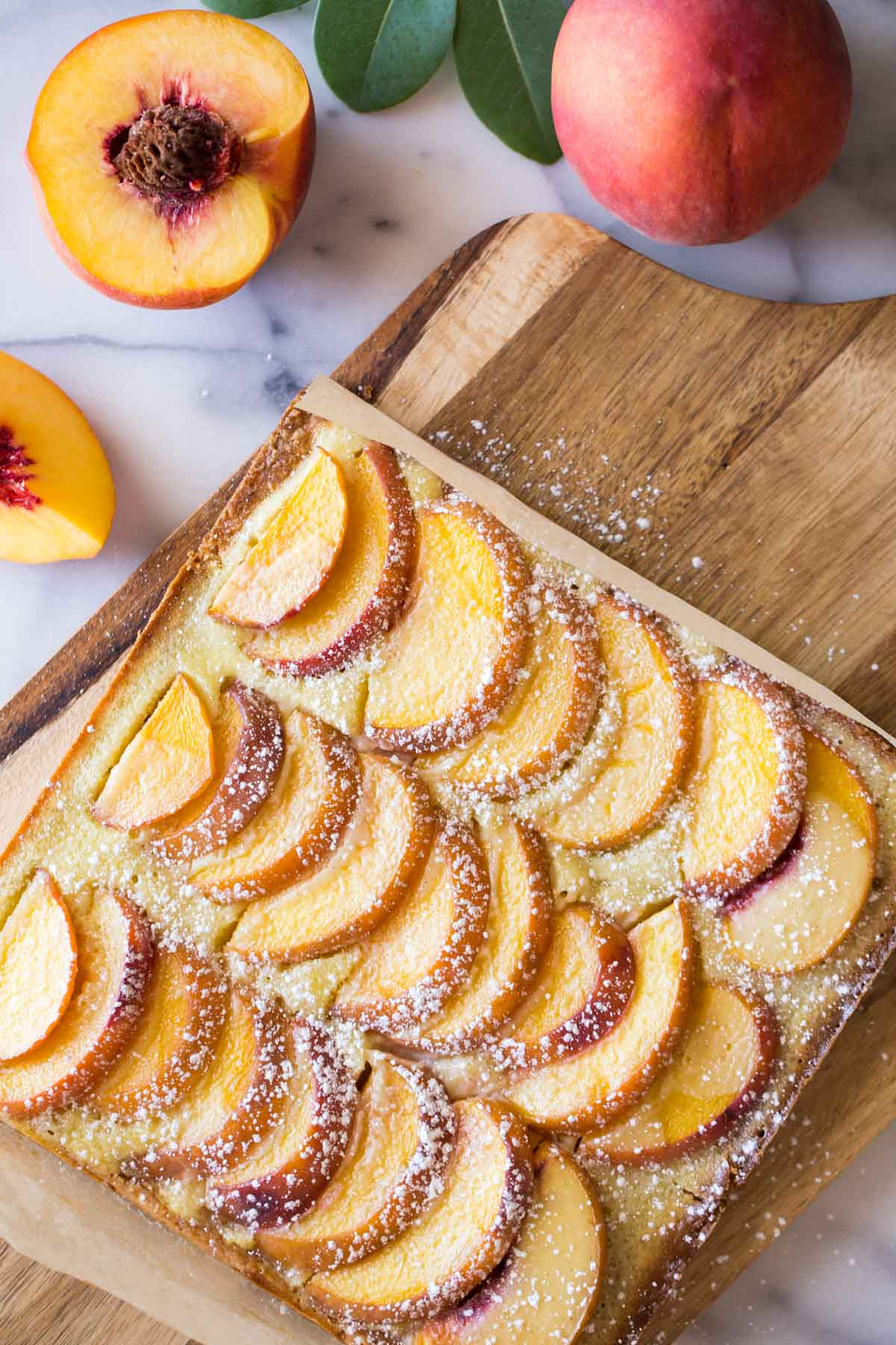 Peaches and Cream Shortbread Bars on a cutting board, with whole and cut peaches next to the board.
