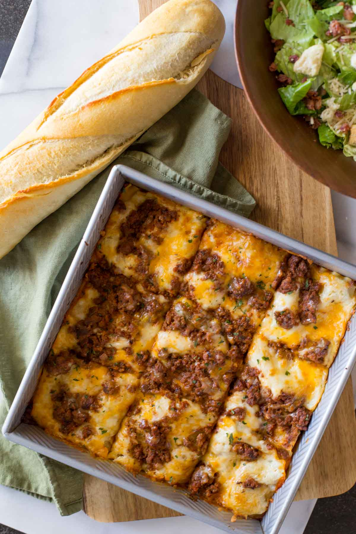 Simple Homemade Lasagna in a square baking dish, with a loaf of French bread and a bowl of salad next to it.