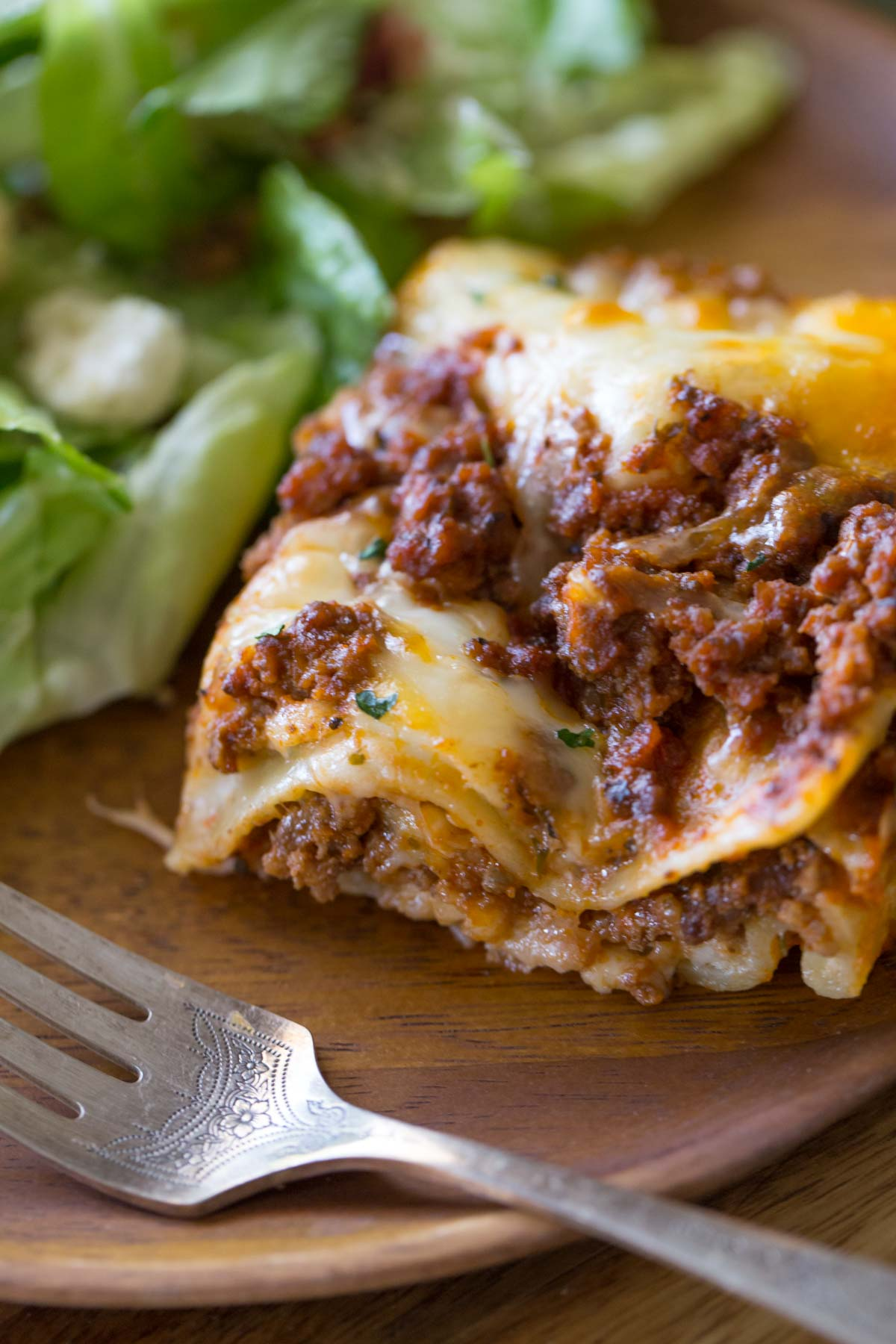 A piece of Simple Homemade Lasagna on a wood plate with a fork and salad.
