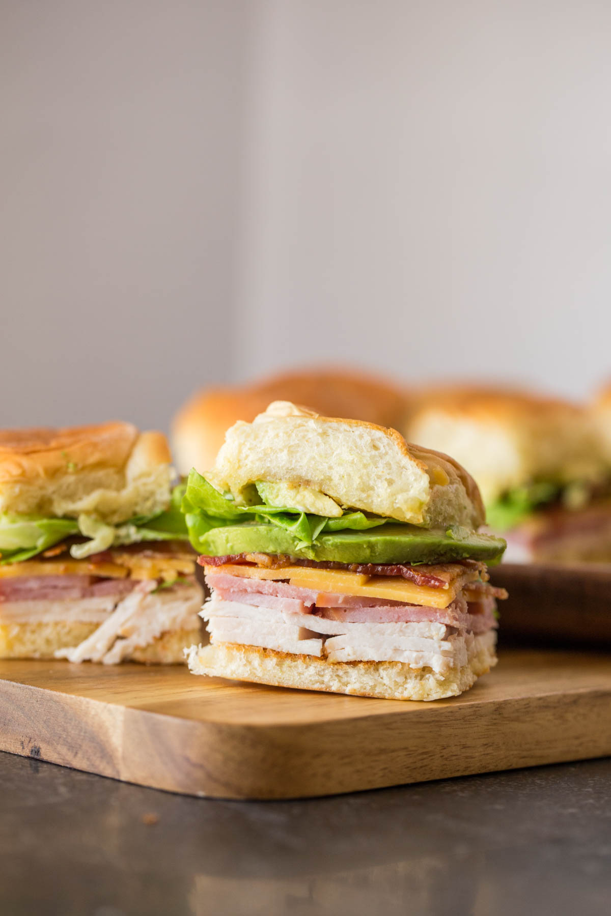 Ultimate Club Sandwiches for a Crowd on a cutting board.