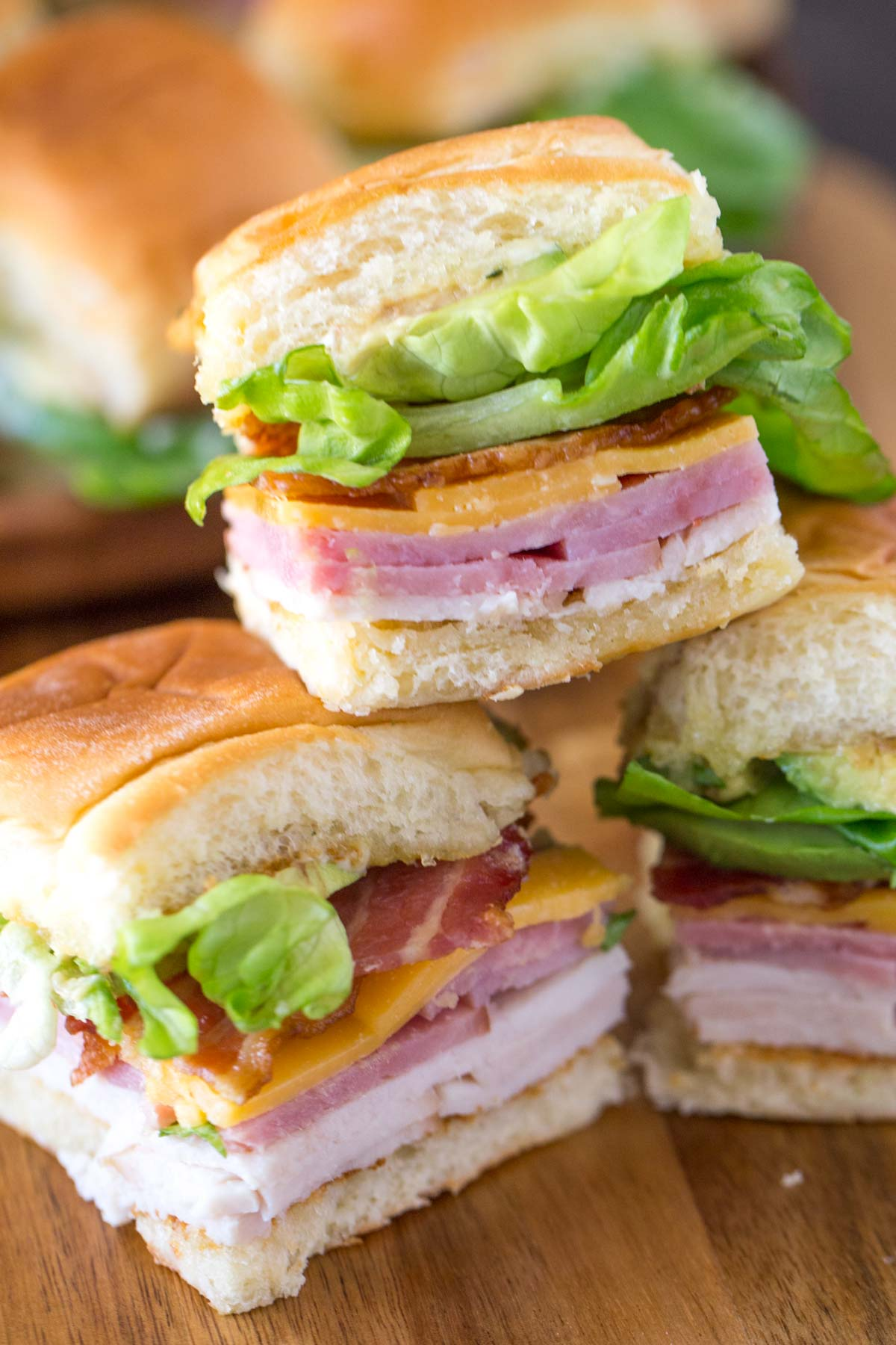 Ultimate Club Sandwiches for a Crowd stacked on a cutting board.