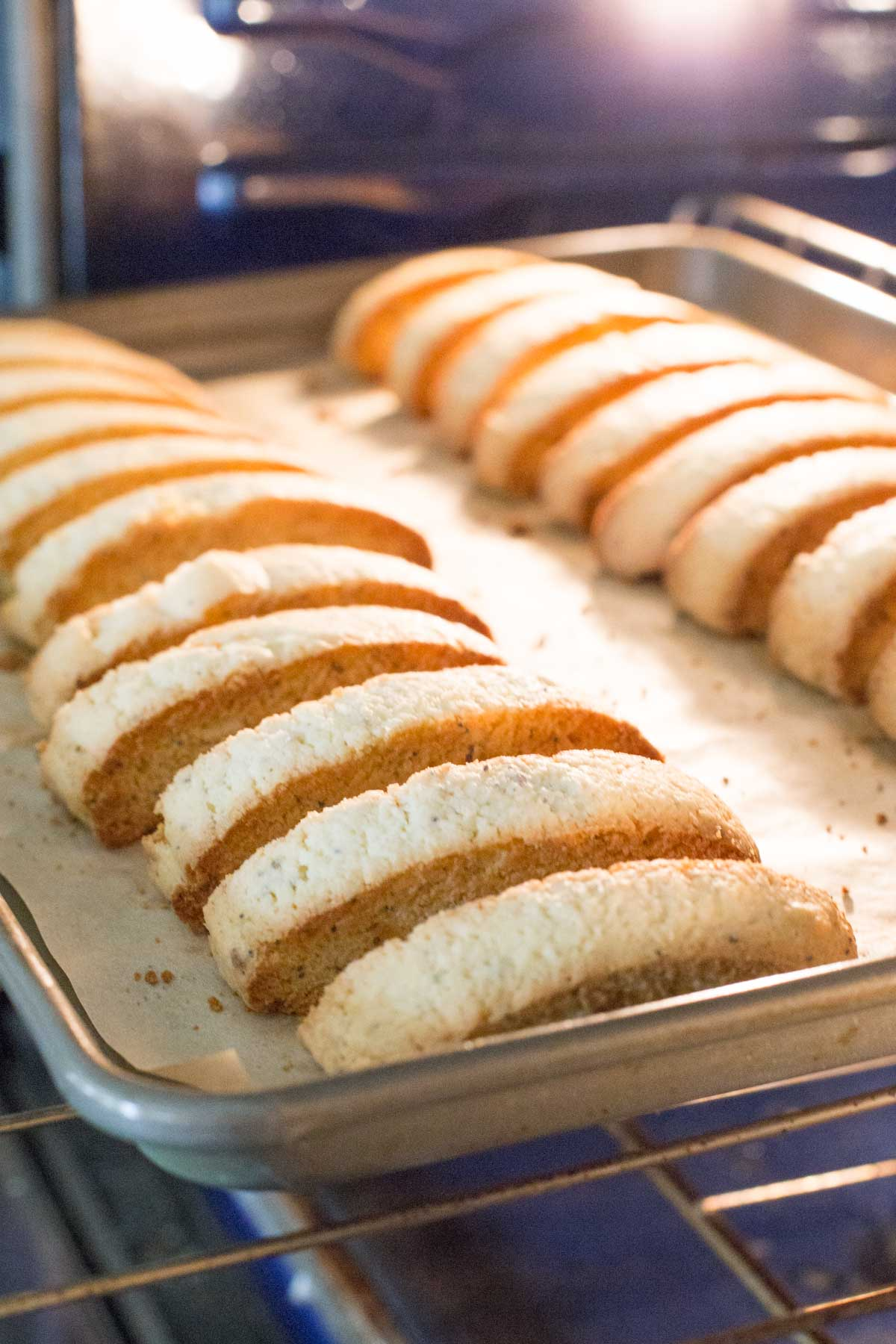 Almond Poppy Seed Biscotti on a parchment paper lined baking sheet in the oven.