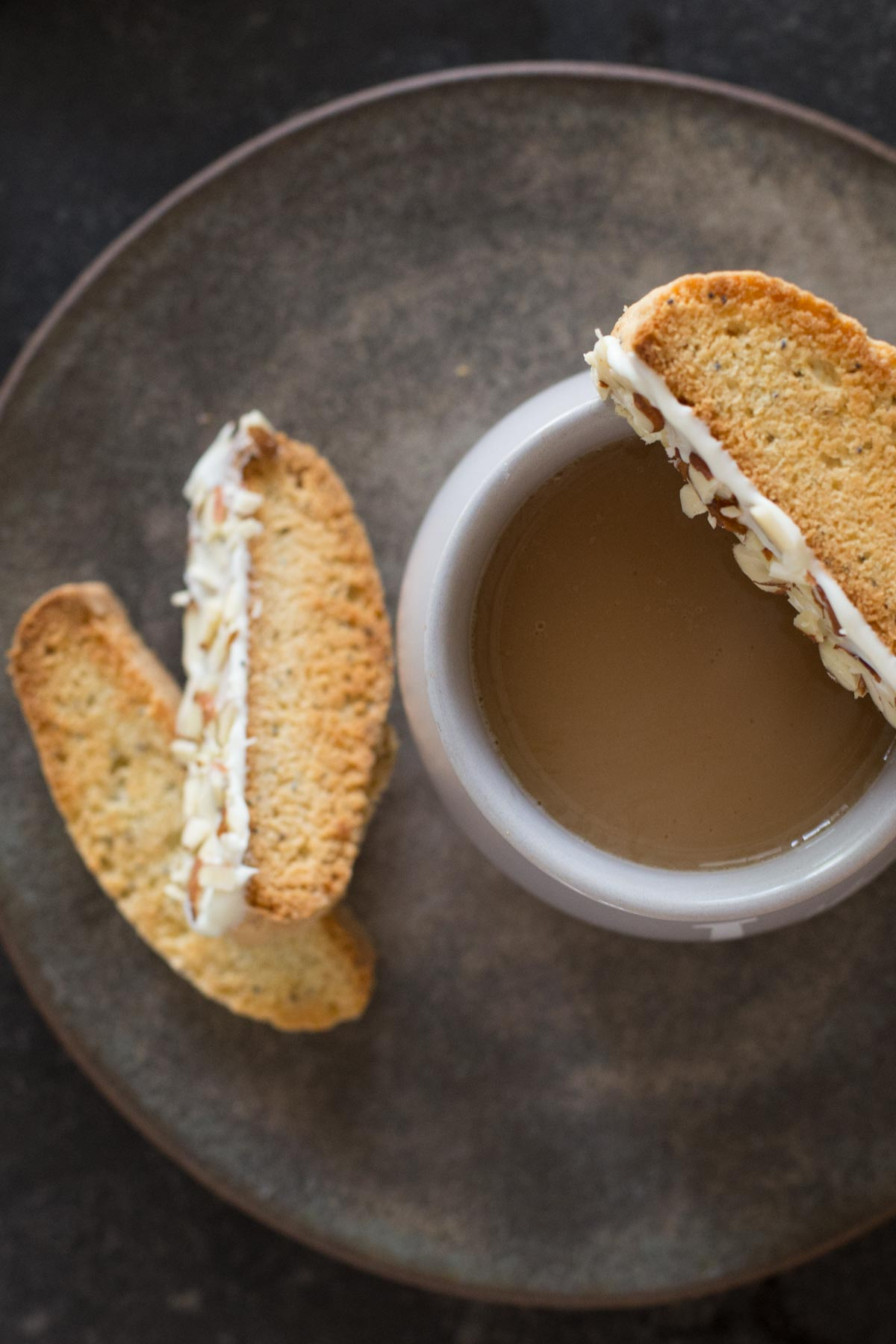 Two Almond Poppy Seed Biscotti slices on a plate, along with a cup of coffee with an Almond Poppy Seed Biscotti slice balancing on the rim of the cup.