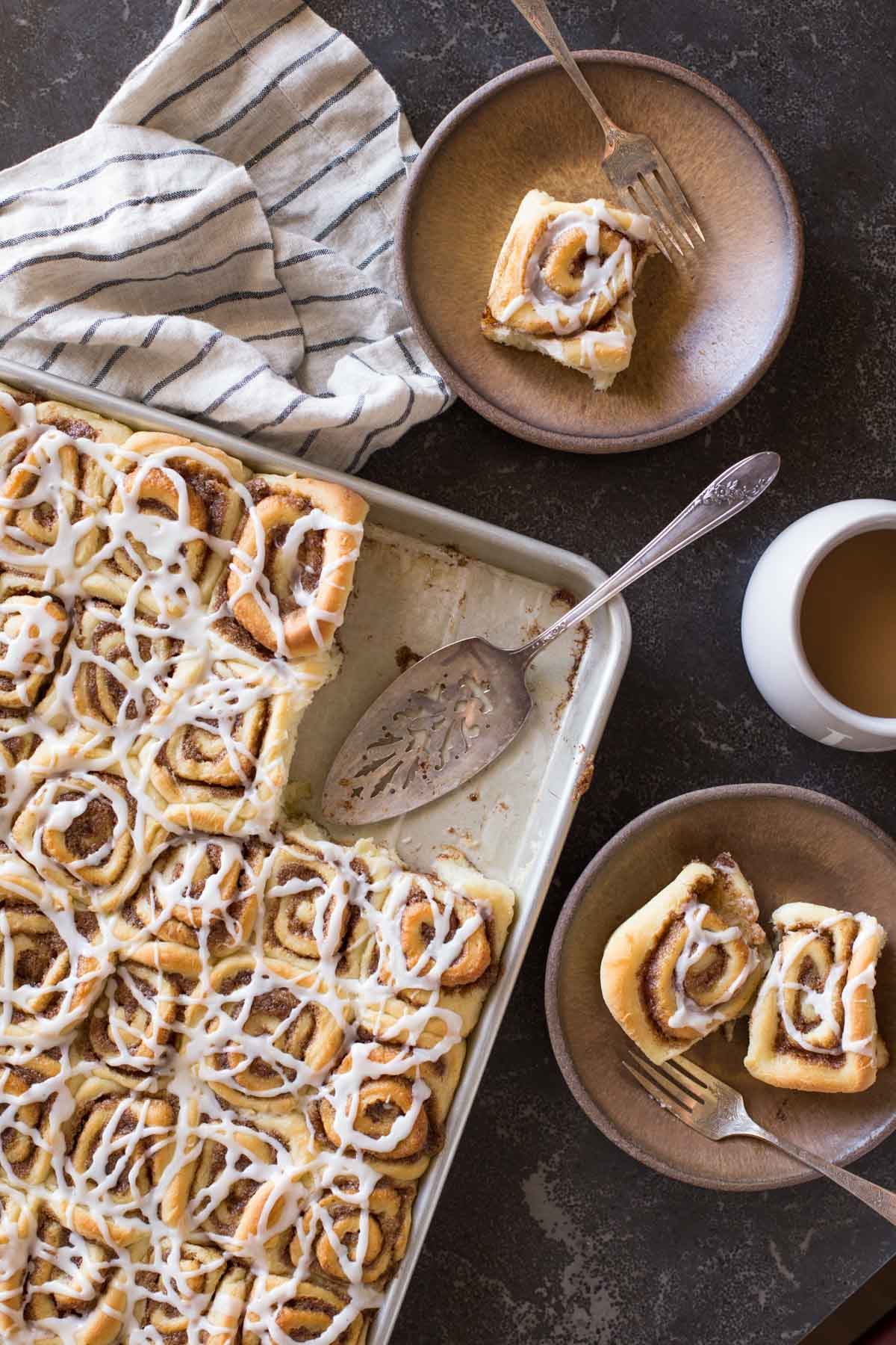 Sheet Pan Cinnamon Rolls on two plates with forks, sitting next to a cup of coffee and the baking sheet of the rest of the cinnamon rolls with a serving utensil.