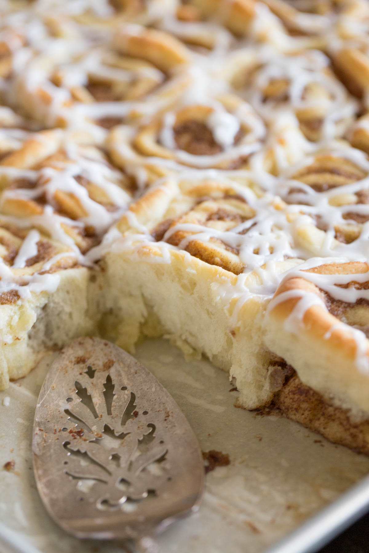 Sheet Pan Cinnamon Rolls in the baking sheet with a serving utensil and some of the rolls missing.
