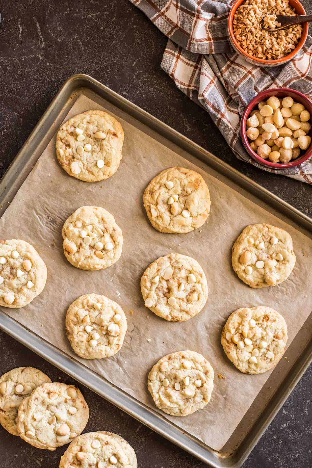 Buttery Toffee White Chocolate Chip Macadamia Nut Cookies on a parchment paper lined baking sheet, with more cookies sitting next to the pan, as well as a bowl of roasted salted macadamia nuts and a bowl of toffee bits.