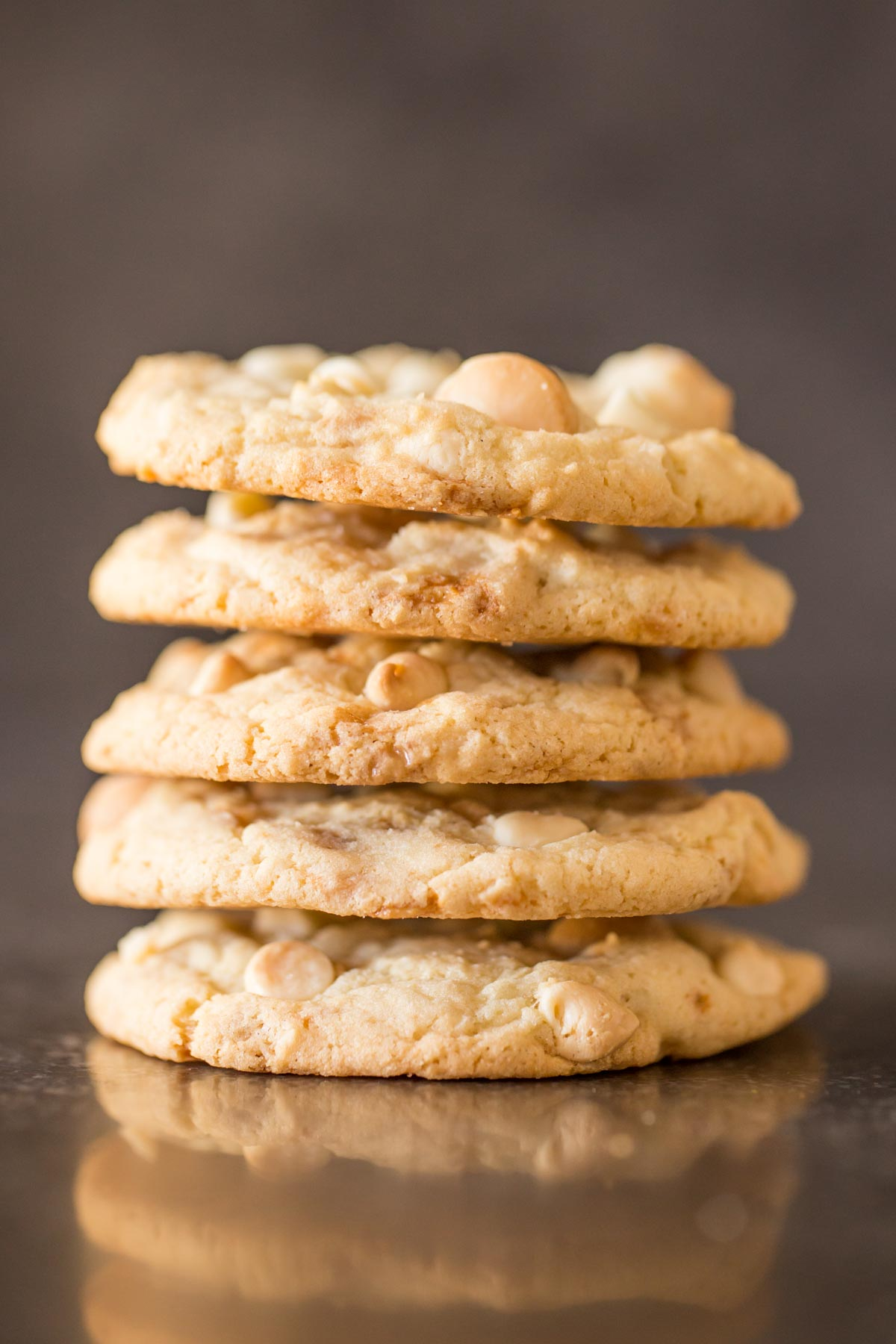 Five Buttery Toffee White Chocolate Chip Macadamia Nut Cookies stacked on top of each other.