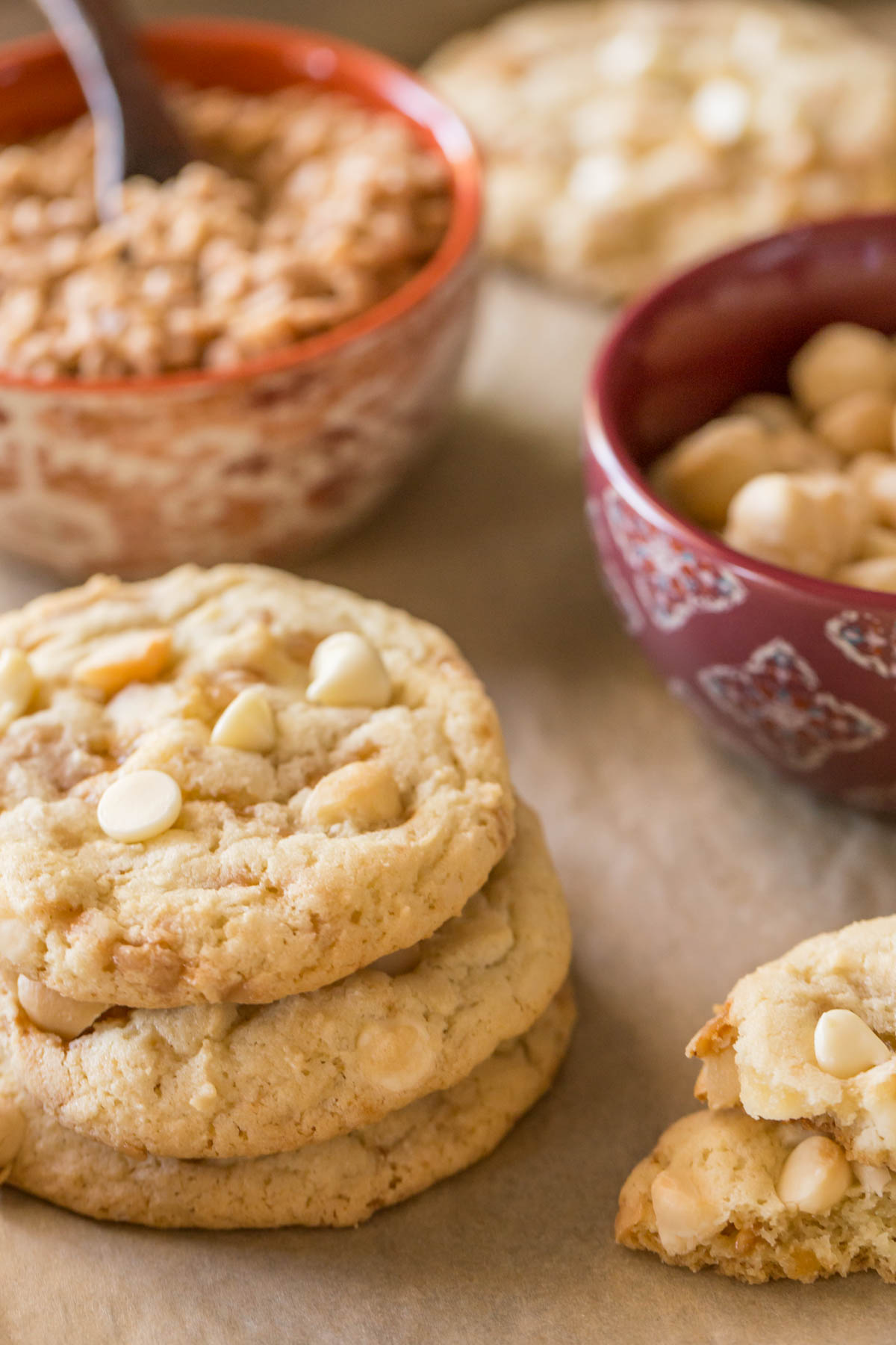 Three Buttery Toffee White Chocolate Chip Macadamia Nut Cookies stacked on top of each other, with a bowl of roasted salted macadamia nuts and a bowl of toffee bits in the background.