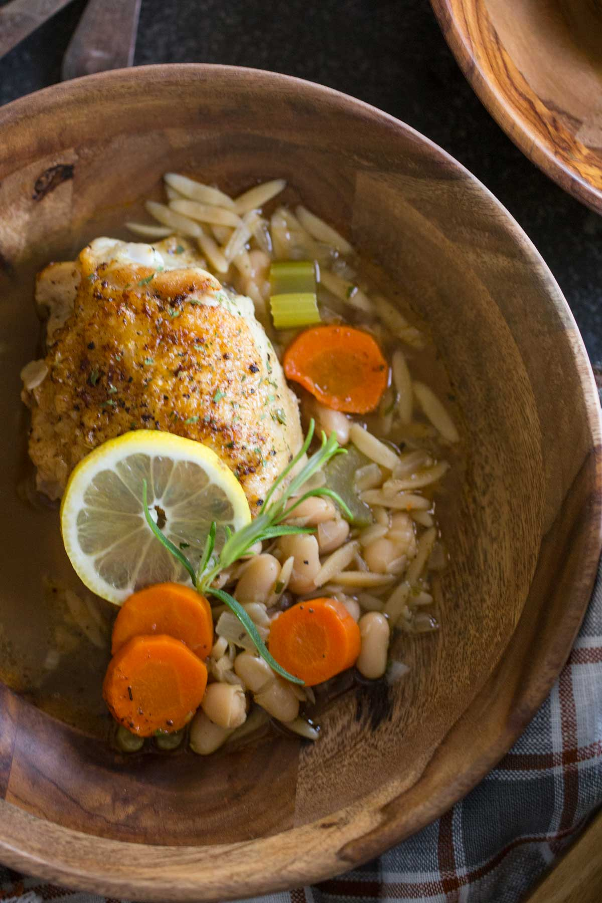 Rustic Lemon Rosemary Chicken and Orzo in a wood bowl, garnished with rosemary and a lemon slice.