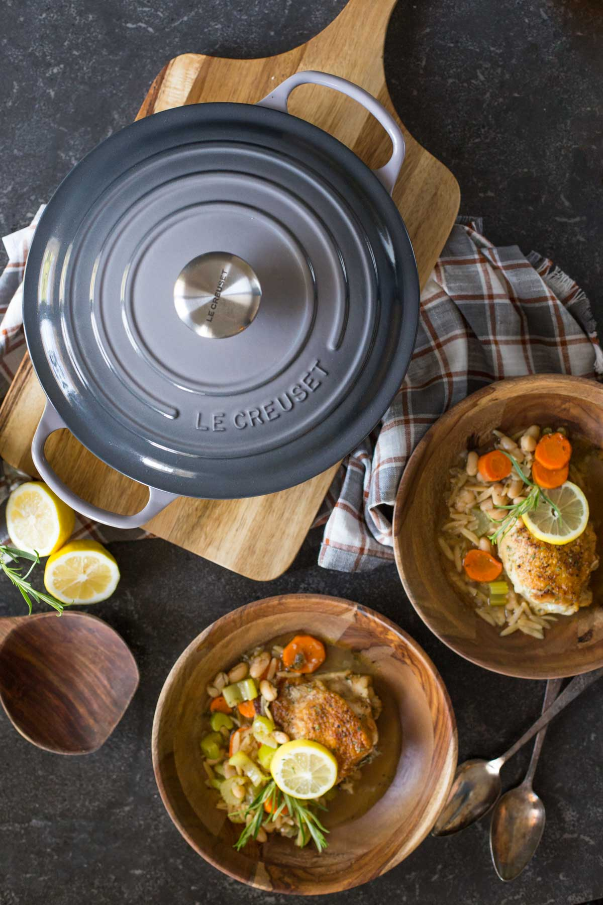 Rustic Lemon Rosemary Chicken and Orzo dished into two wood bowls, sitting next to a Le Creuset Dutch oven with the lid on.