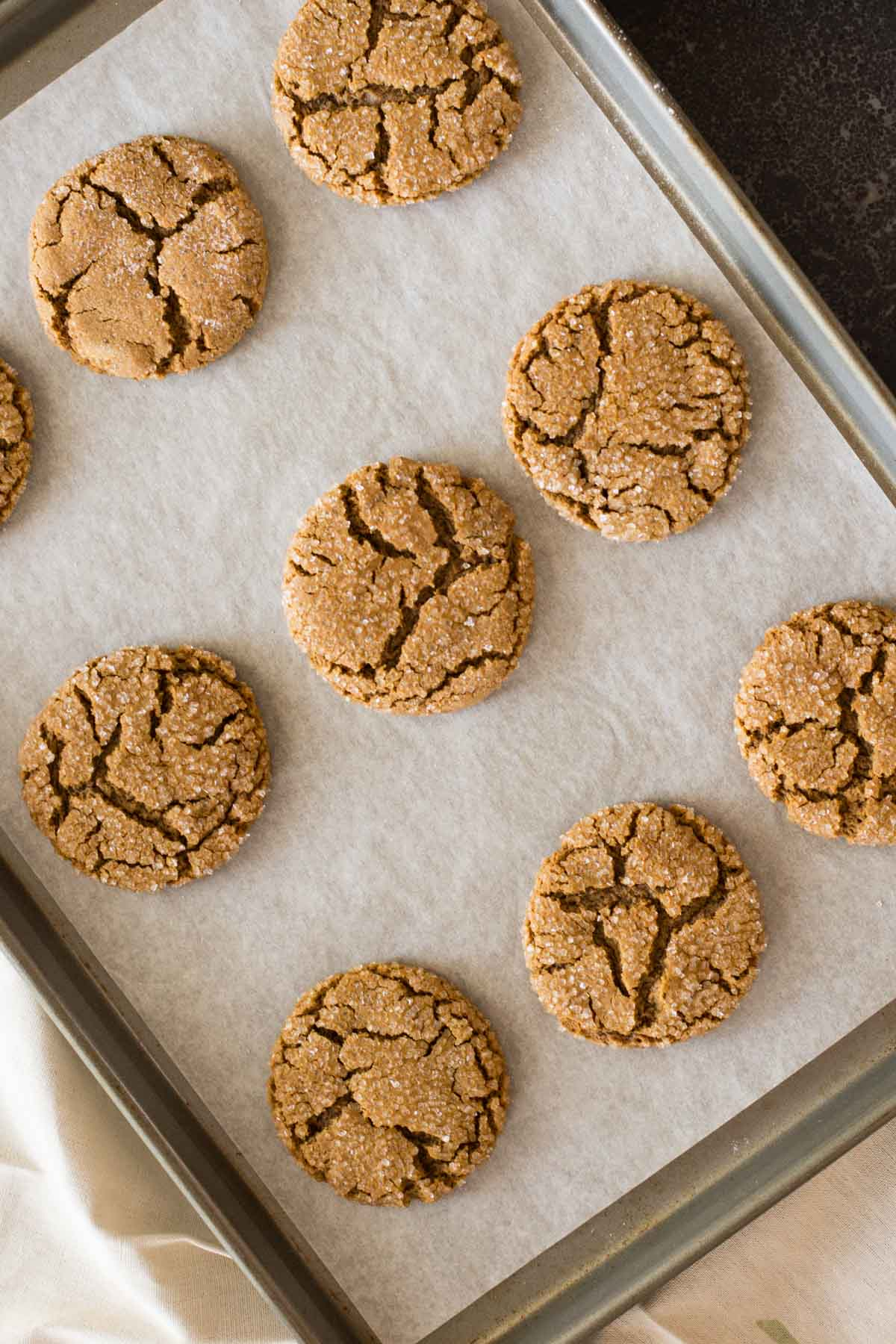Peanut Butter Molasses Cookies on a parchment paper lined baking sheet.