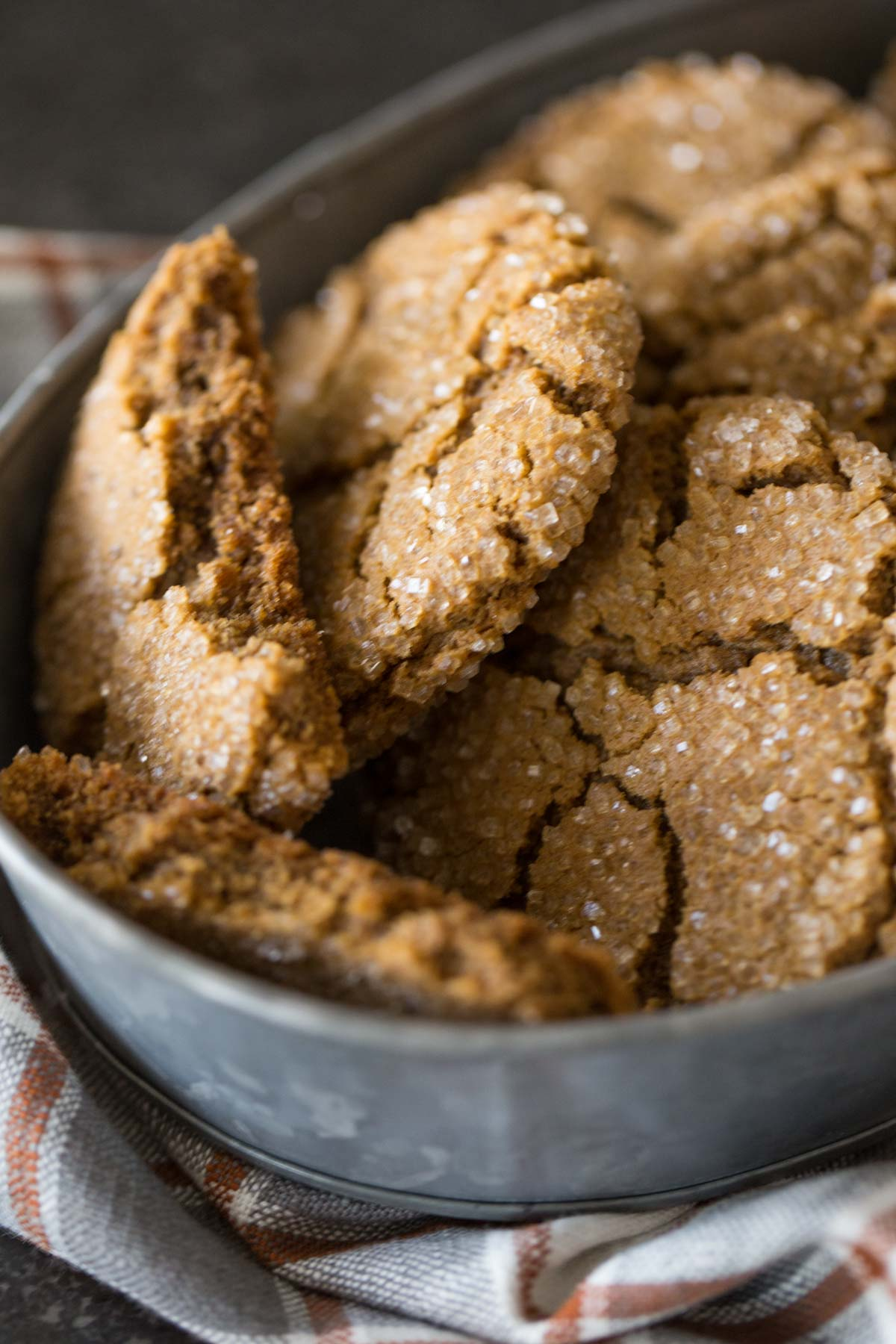 Peanut Butter Molasses Cookies in a galvanized bowl, with one of the cookies broken in half.