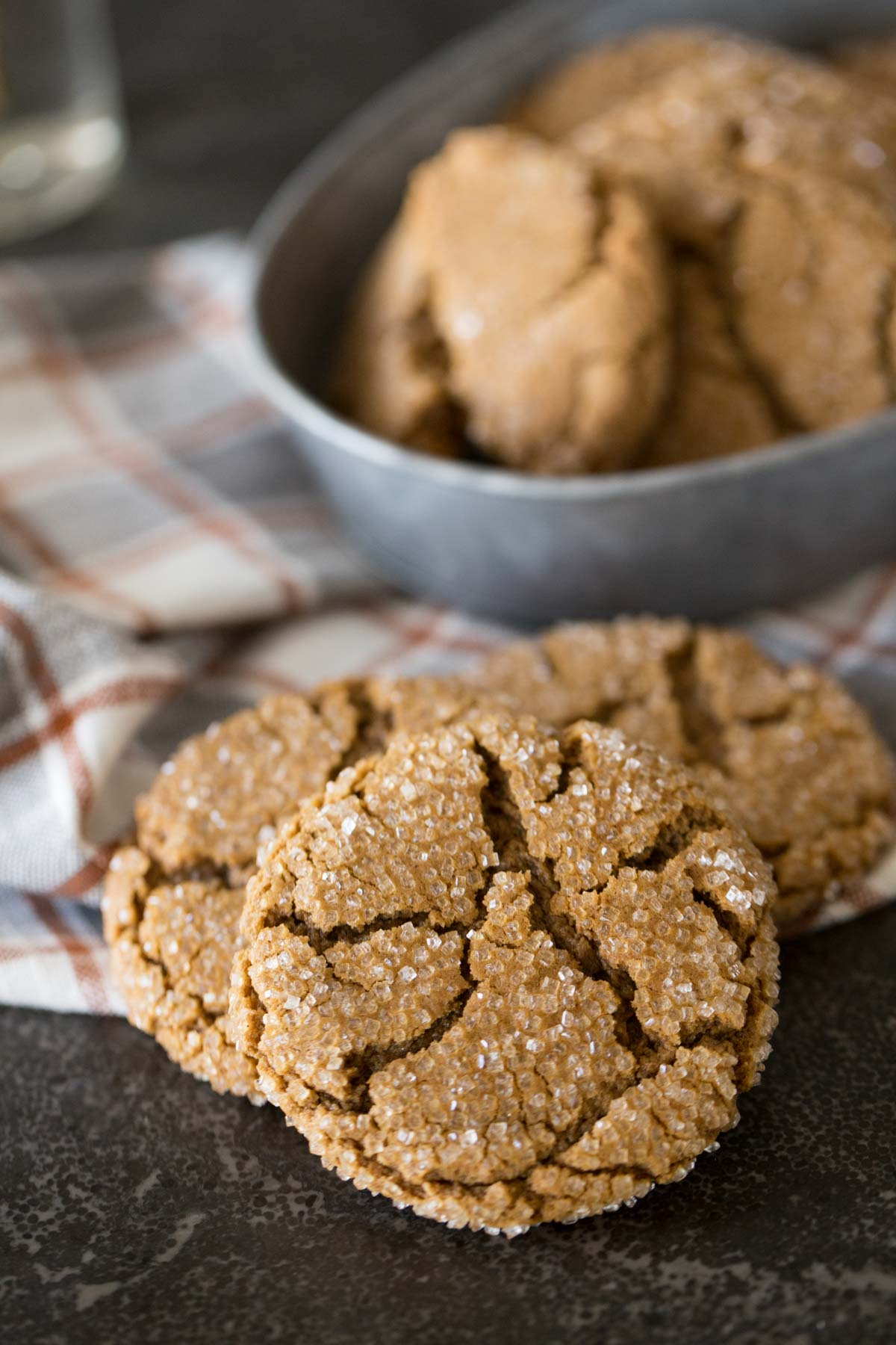 Three Peanut Butter Molasses Cookies with more cookies in a galvanized bowl in the background.