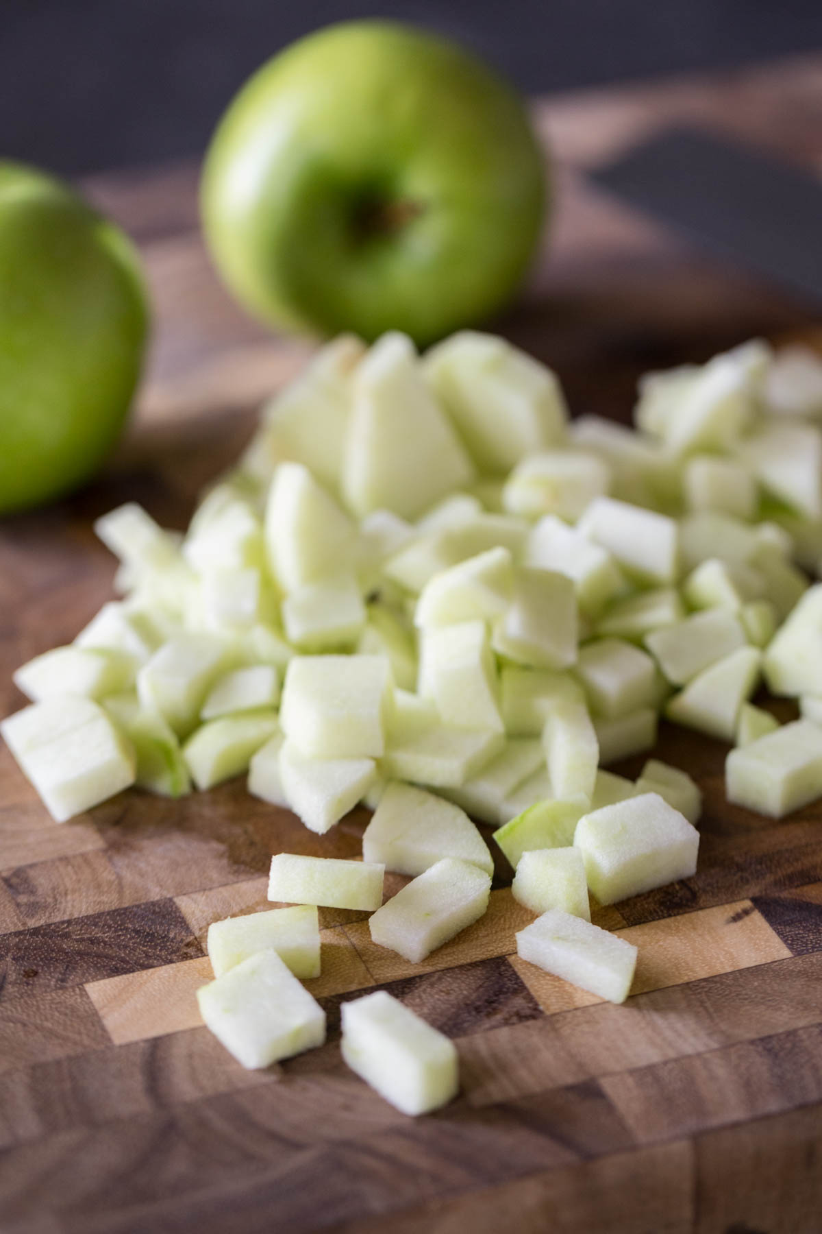 Peeled and chopped Granny Smith apples on a cutting board, with whole apples in the background.