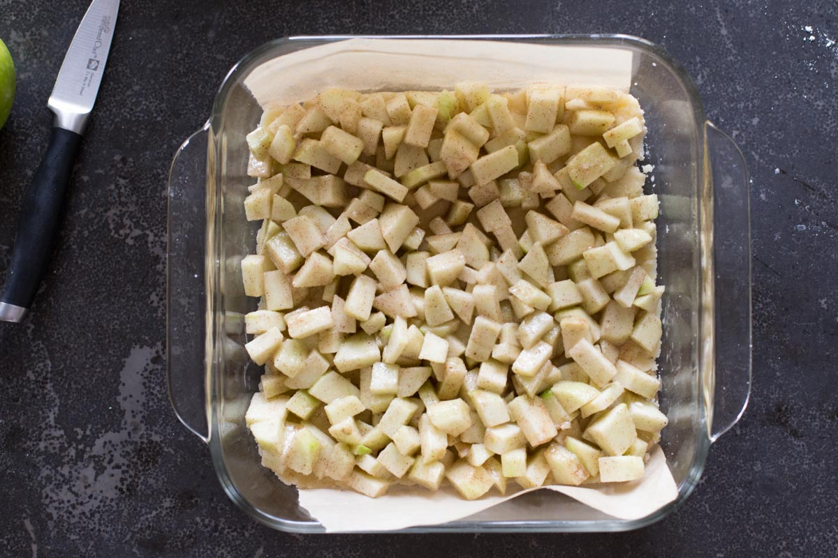 The Apple Pie Crumb Bars filling in a parchment paper lined baking dish.