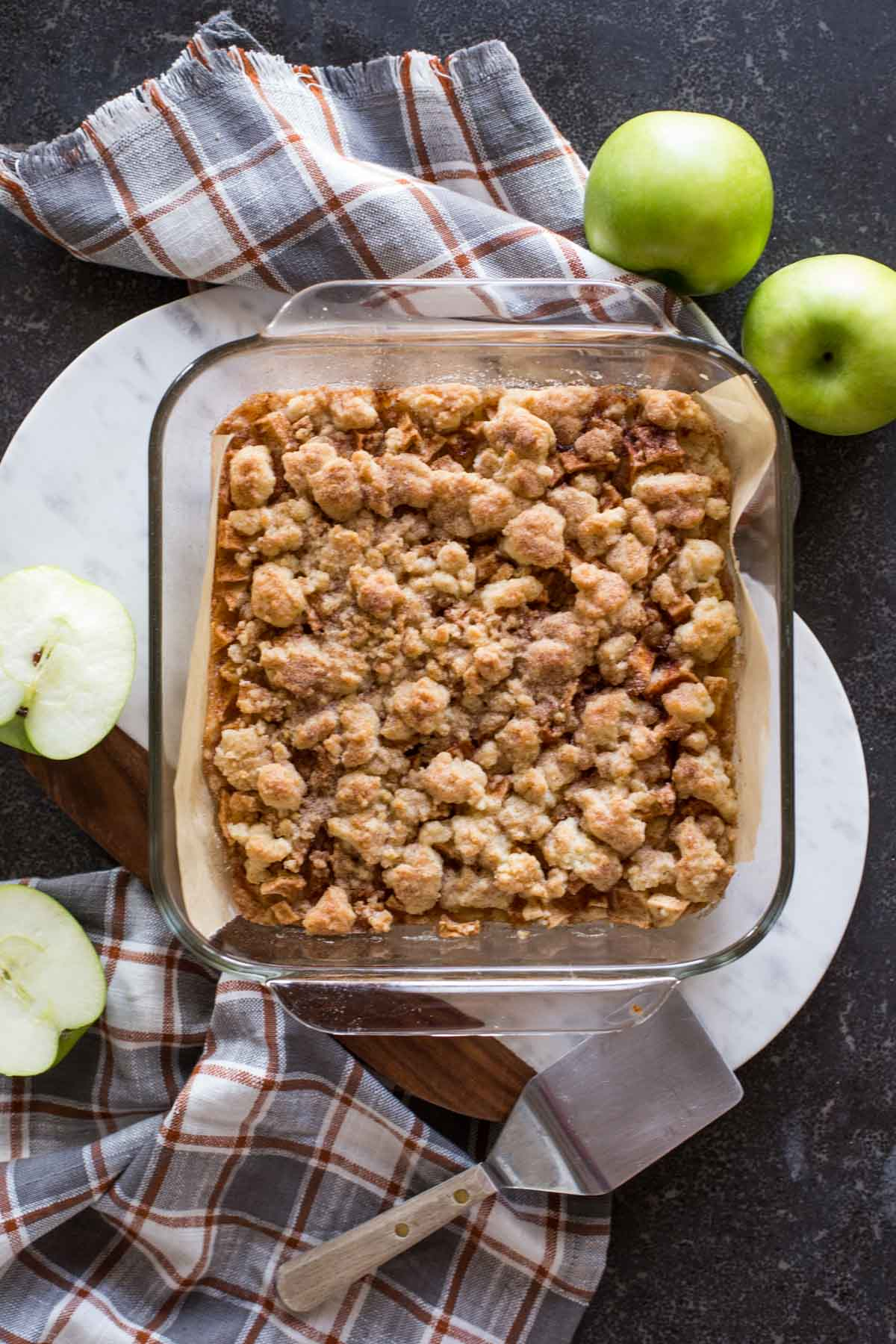 Apple Pie Crumb Bars in a square baking dish, with whole and halved apples next to it, as well as a serving spatula.
