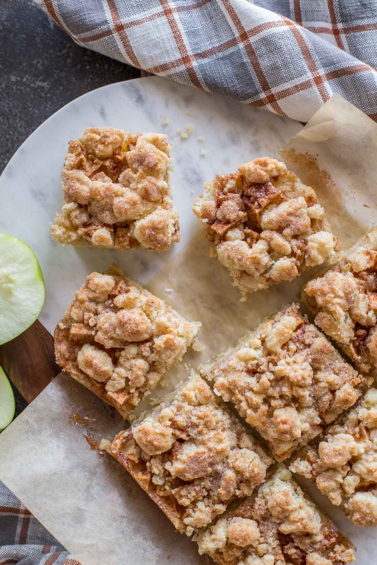 Apple Pie Crumb Bars on a marble and wood cutting board.