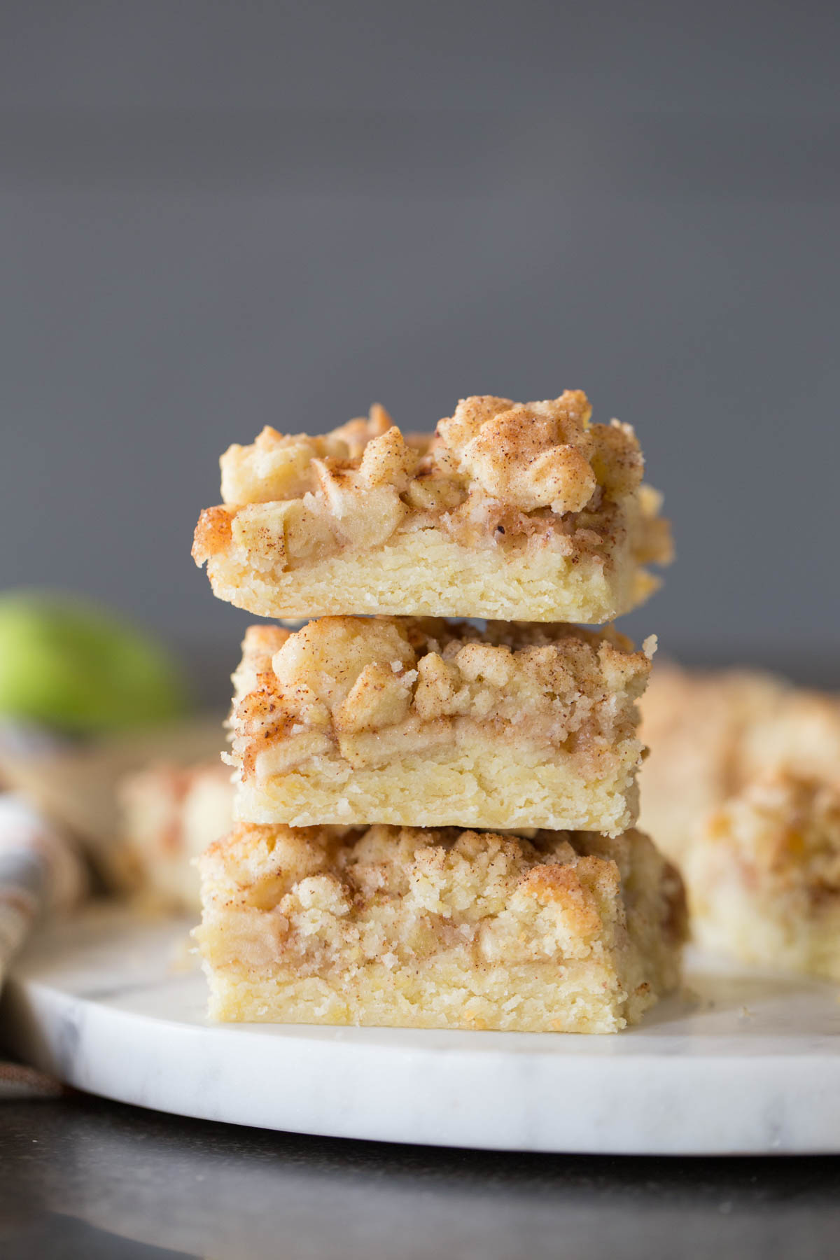Three Apple Pie Crumb Bars stacked on top of each other.