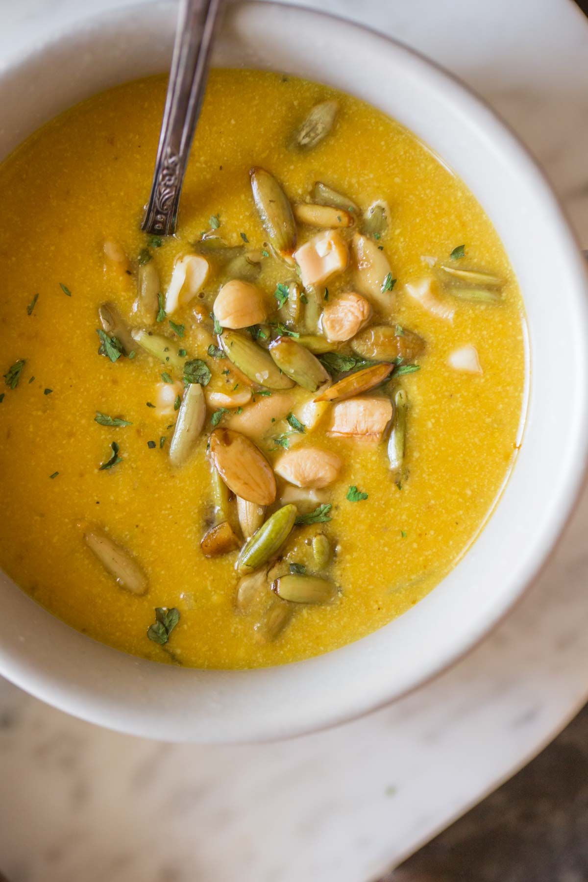 A bowl of Creamy Cashew Pumpkin Soup, garnished with pepitas, chopped cashews and parsley, with a spoon in it.