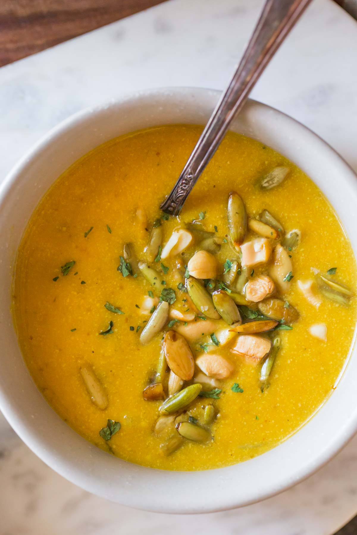 Top down view of a bowl of Creamy Cashew Pumpkin Soup with pepitas and cashews on top.
