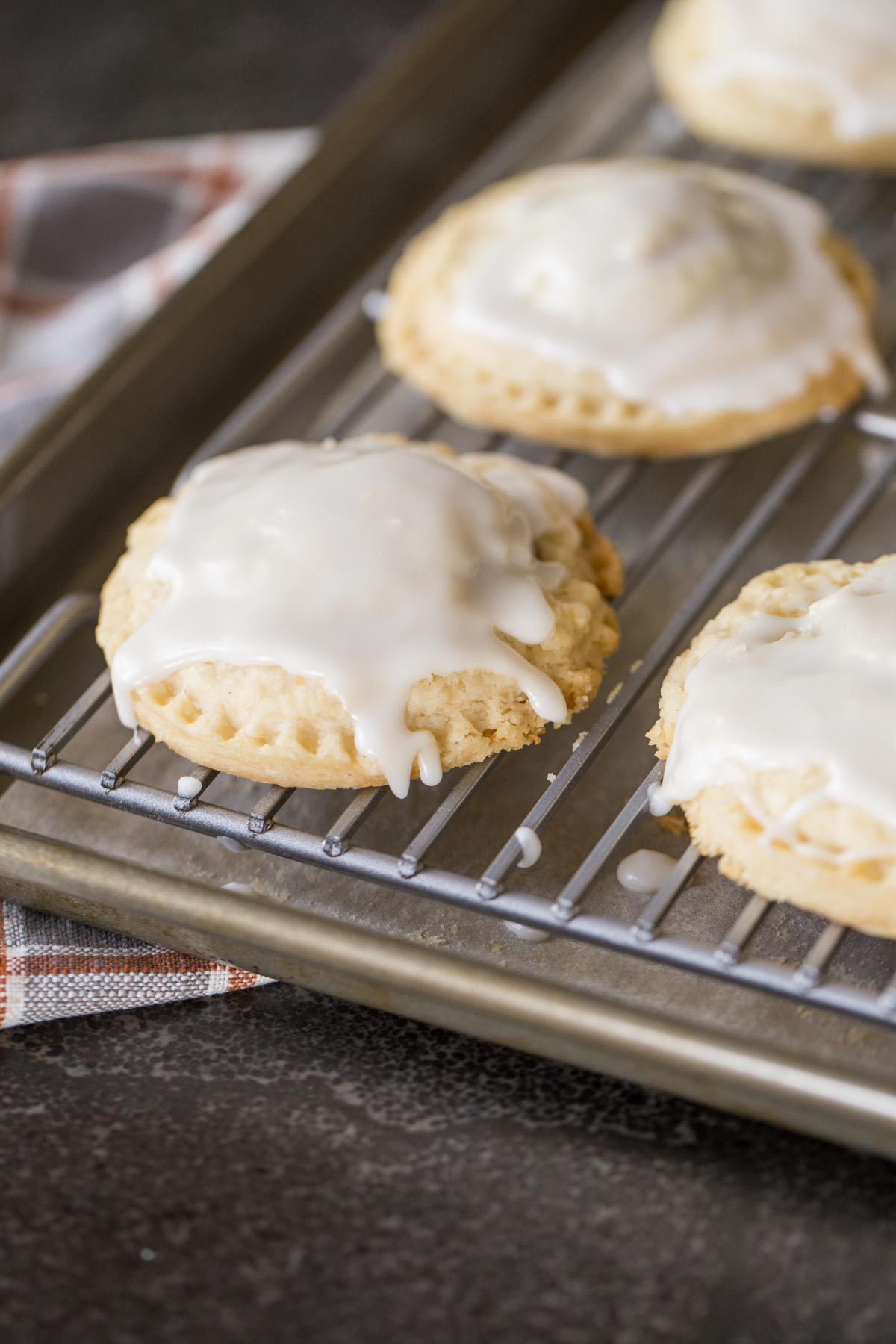 Glazed Pumpkin Hand Pies on a cooling rack that is on a baking sheet.