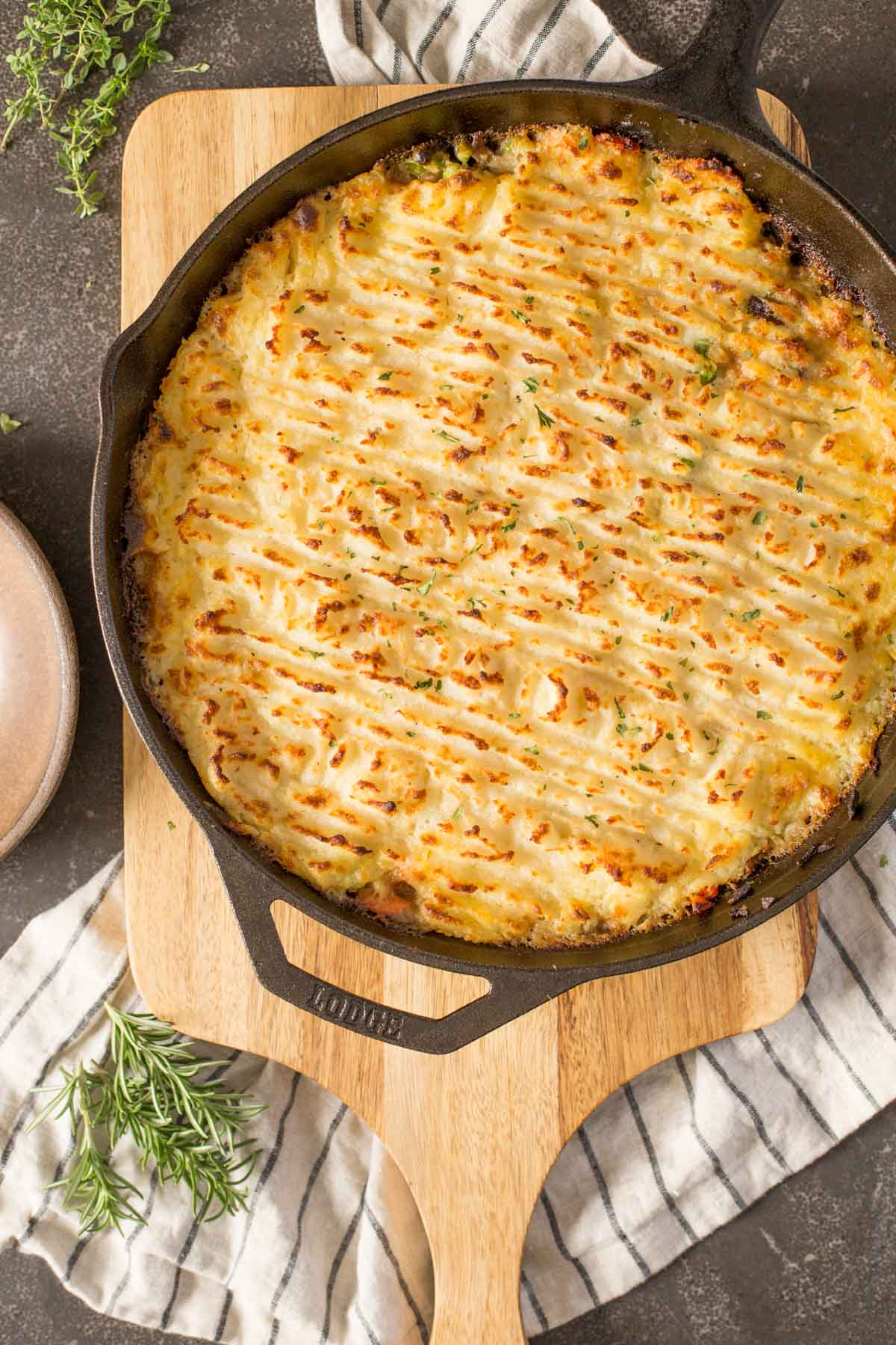 Easy Homemade Shepherd's Pie in a cast iron skillet, sitting on top of a wood cutting board.
