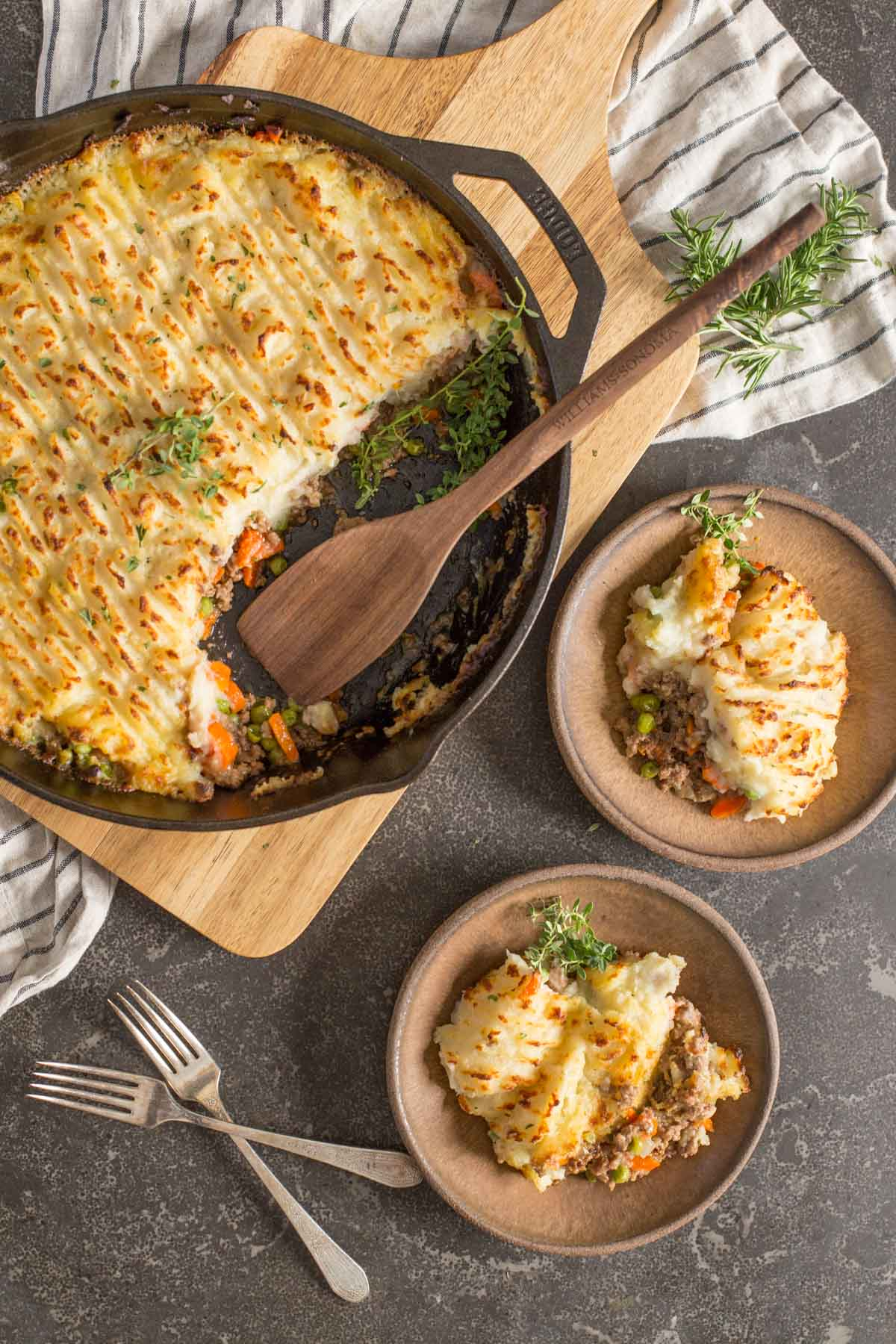 Two servings of Easy Homemade Shepherd's Pie dished on to two plates, with two forks next to them as well as the cast iron skillet of Easy Homemade Shepherd's Pie with a wooden spoon in it.