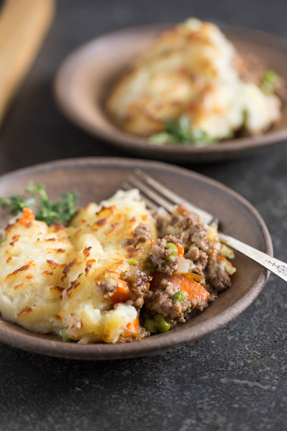 Easy Homemade Shepherd's Pie on a plate with a fork, with another serving of Easy Homemade Shepherd's Pie on a plate in the background.