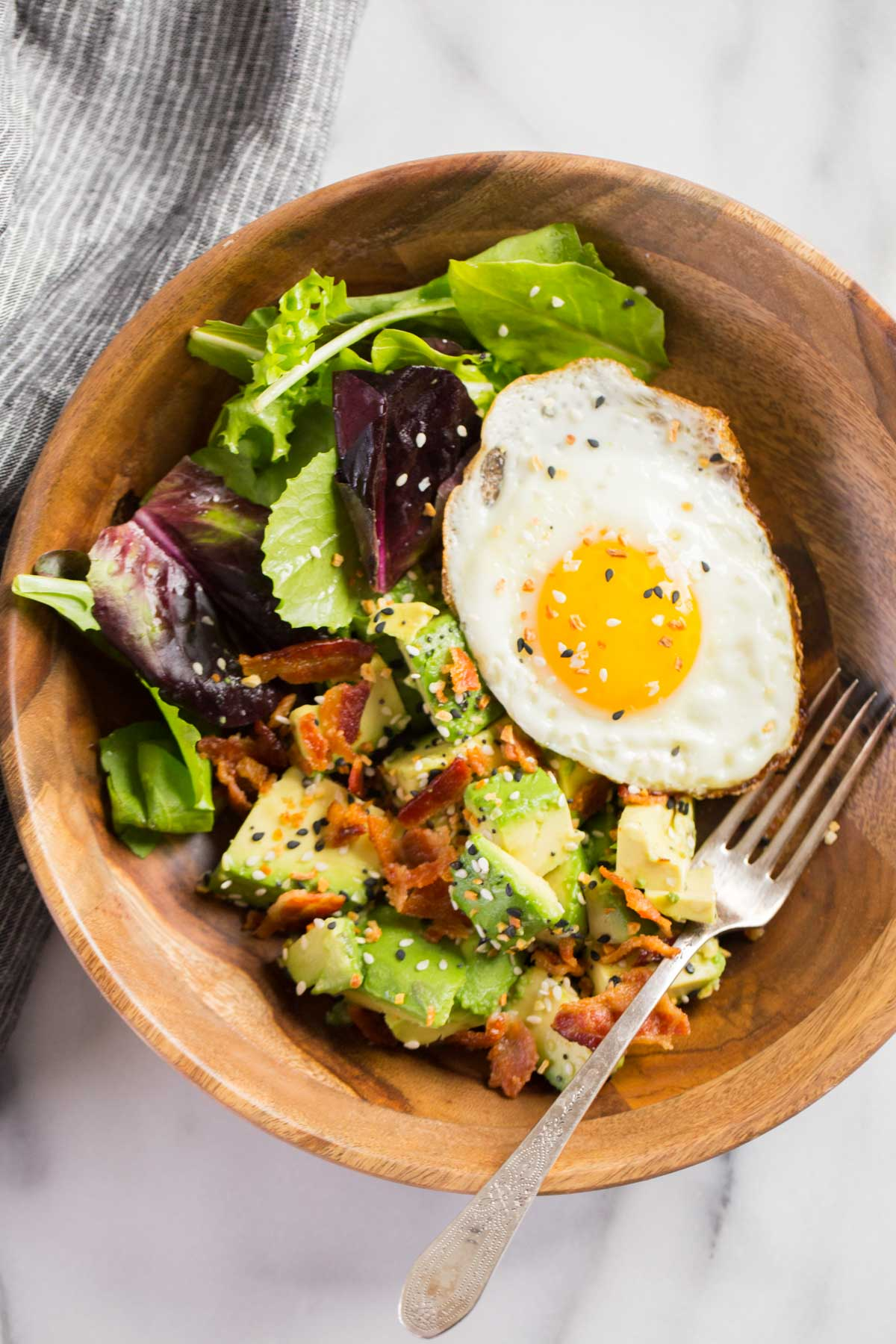 Avocado Breakfast Bowl in a wood bowl with a fork.