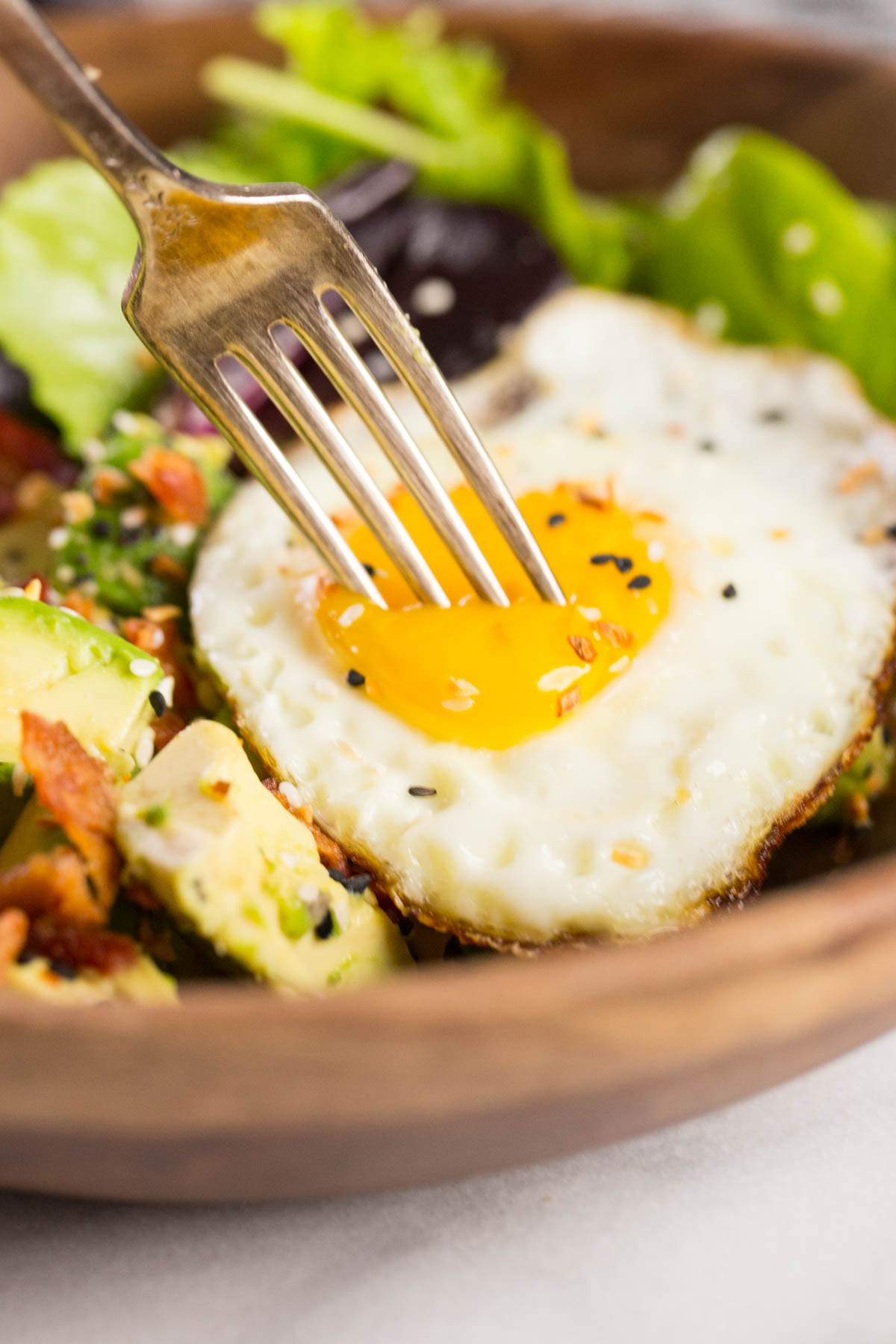 Avocado Breakfast Bowl in a wood bowl with a fork poking into the egg yolk.