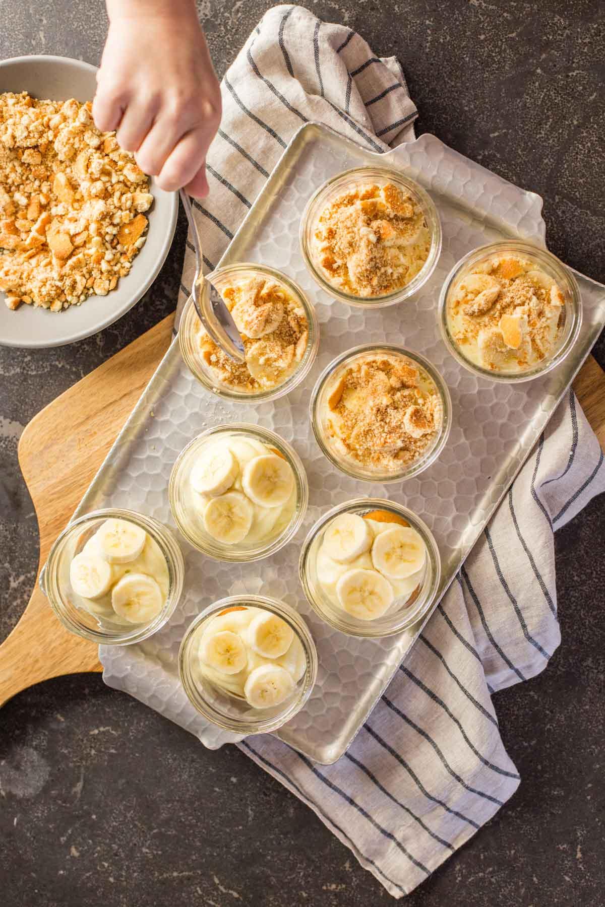 Spooning crushed Nilla wafers into individual banana pudding jars
