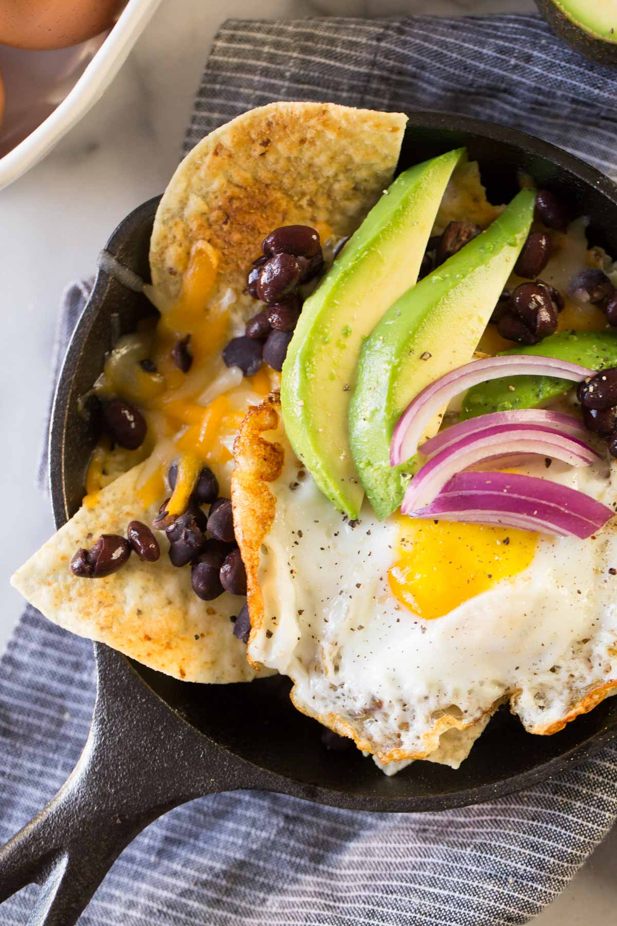 Breakfast Nacho Skillet topped with avocado slices and red onions.