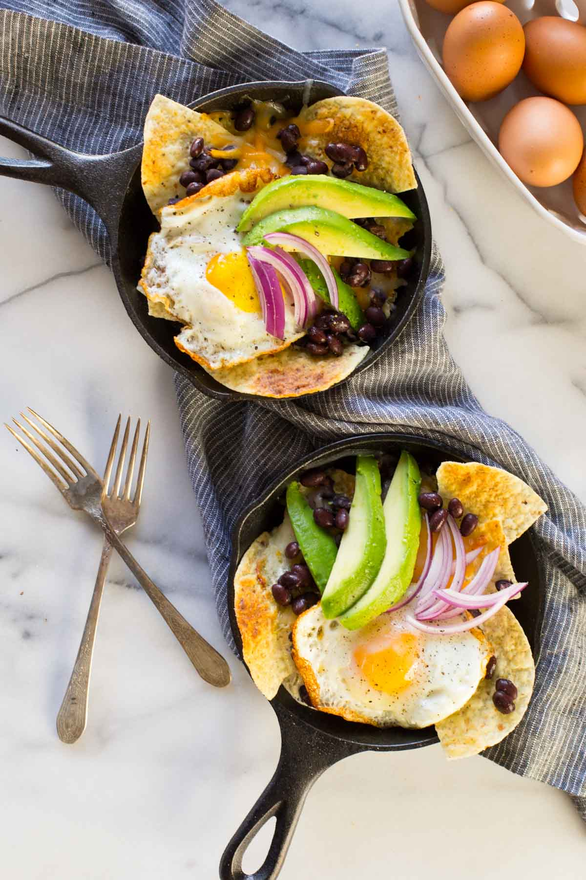 Two Breakfast Nacho Skillets topped with avocado slices and red onions, with two forks and a basket of eggs sitting next to the skillets.