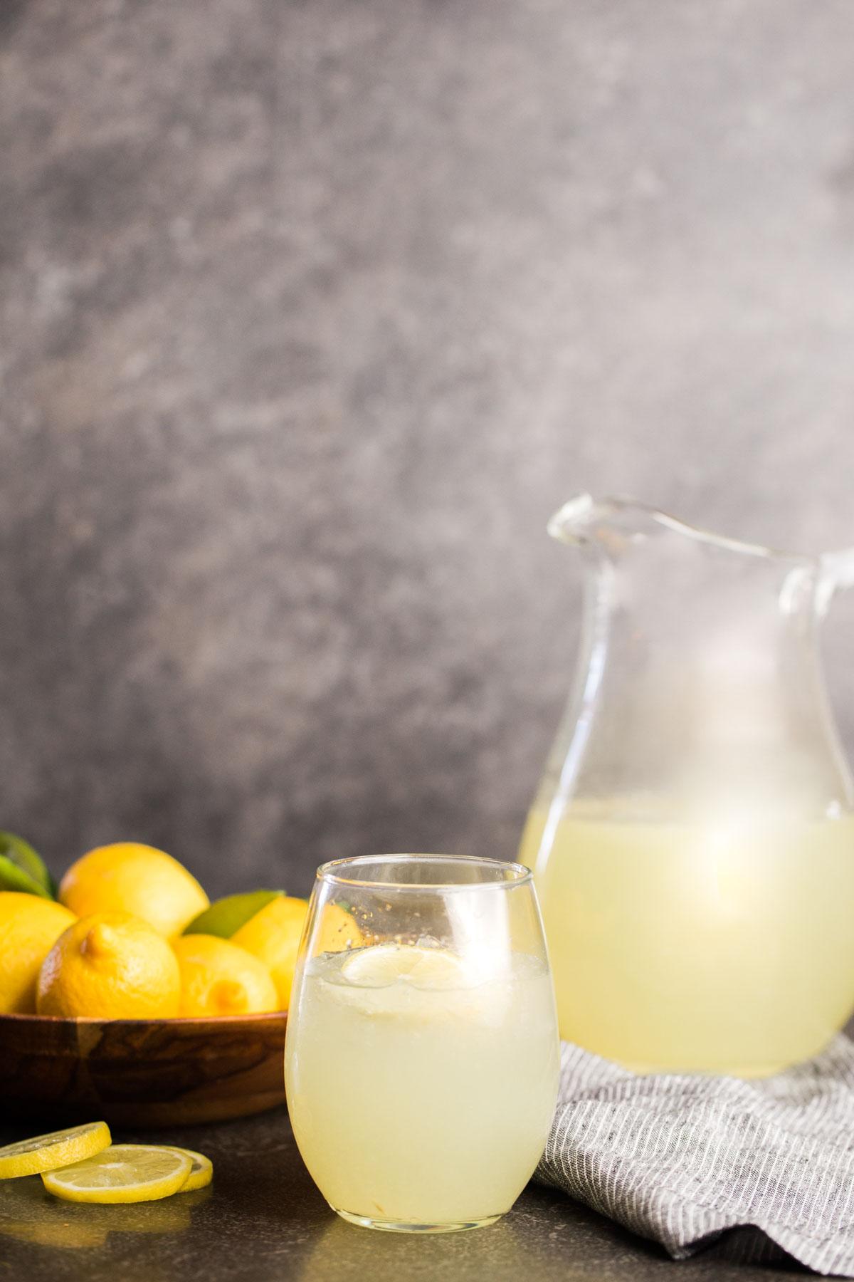 Lemonade in glass pitcher with bowl of lemons and glass of lemonade.