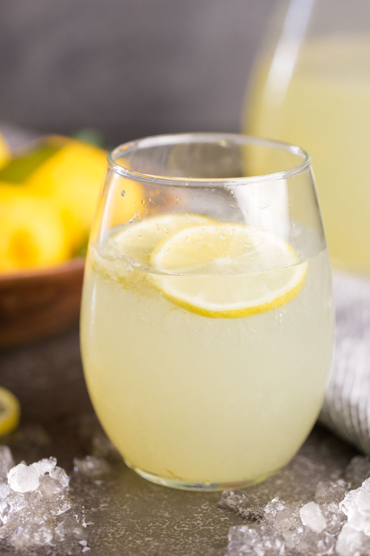 Close up front view of glass of lemonade with lemon slices and crushed ice.