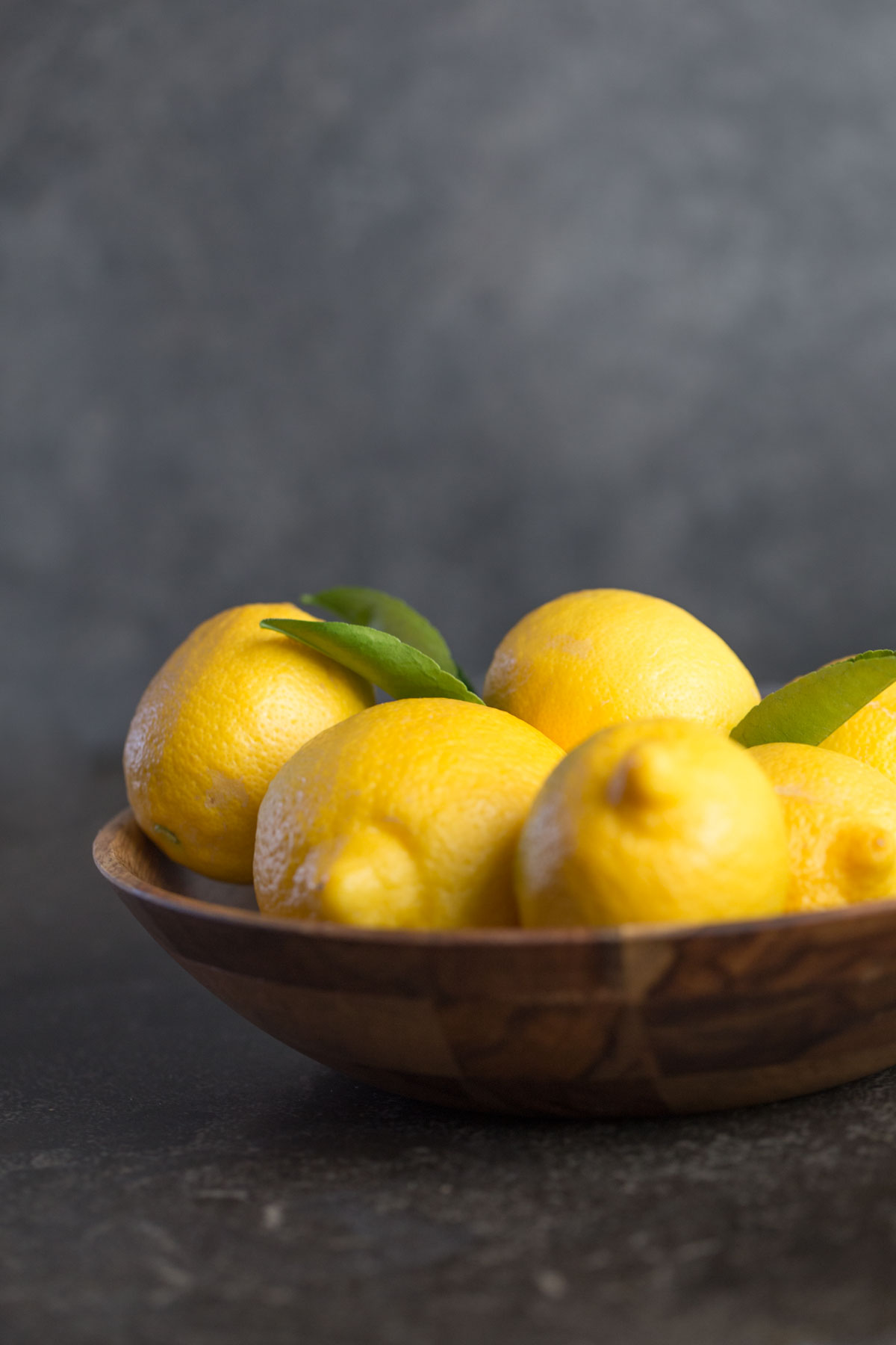 Wooden bowl of lemons with leaves attached from the front view with a dark grey background.