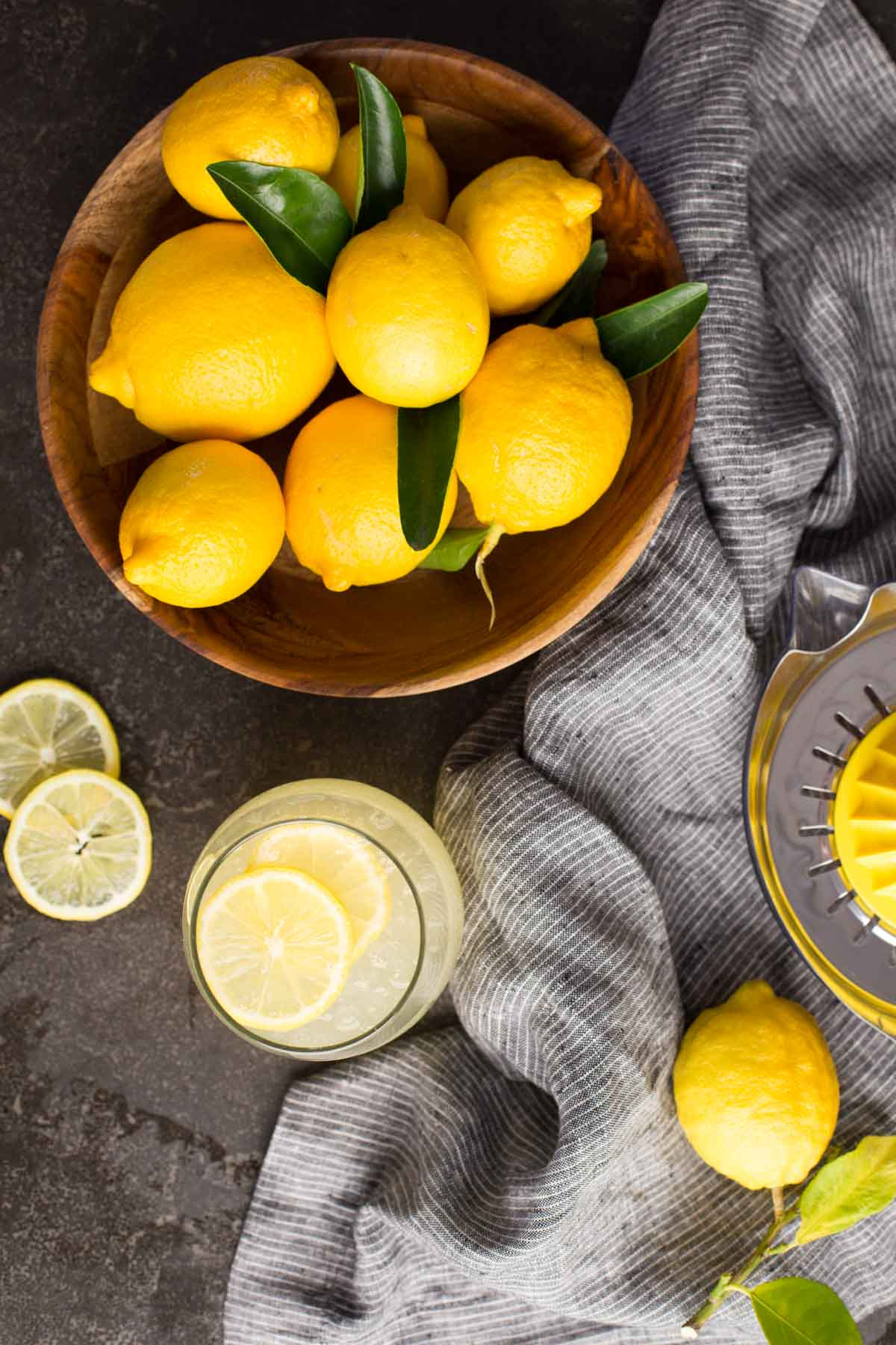 Top down view of wooden bowl of lemons with a glass of lemonade and lemon slices.