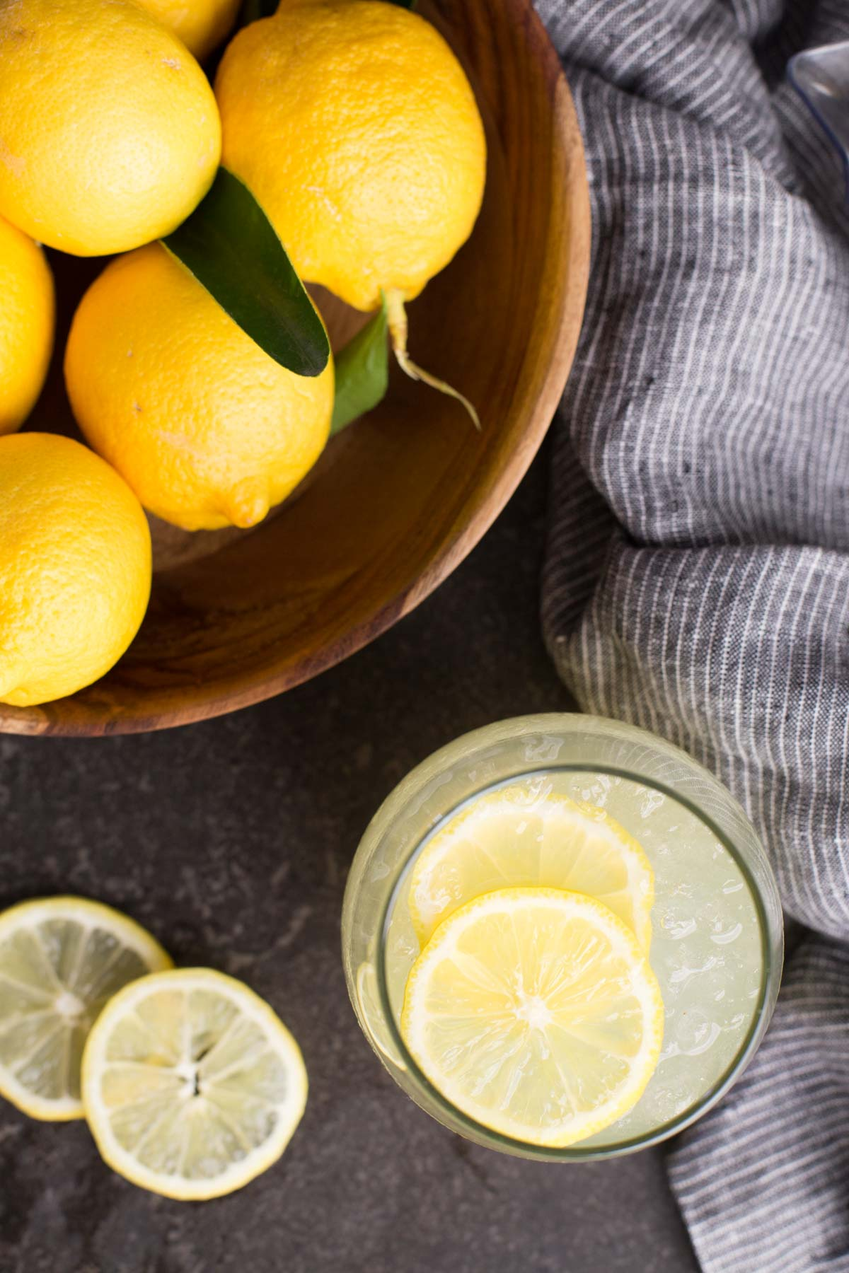Wooden bowl of freshly picked lemons and a glass of lemonade poured.