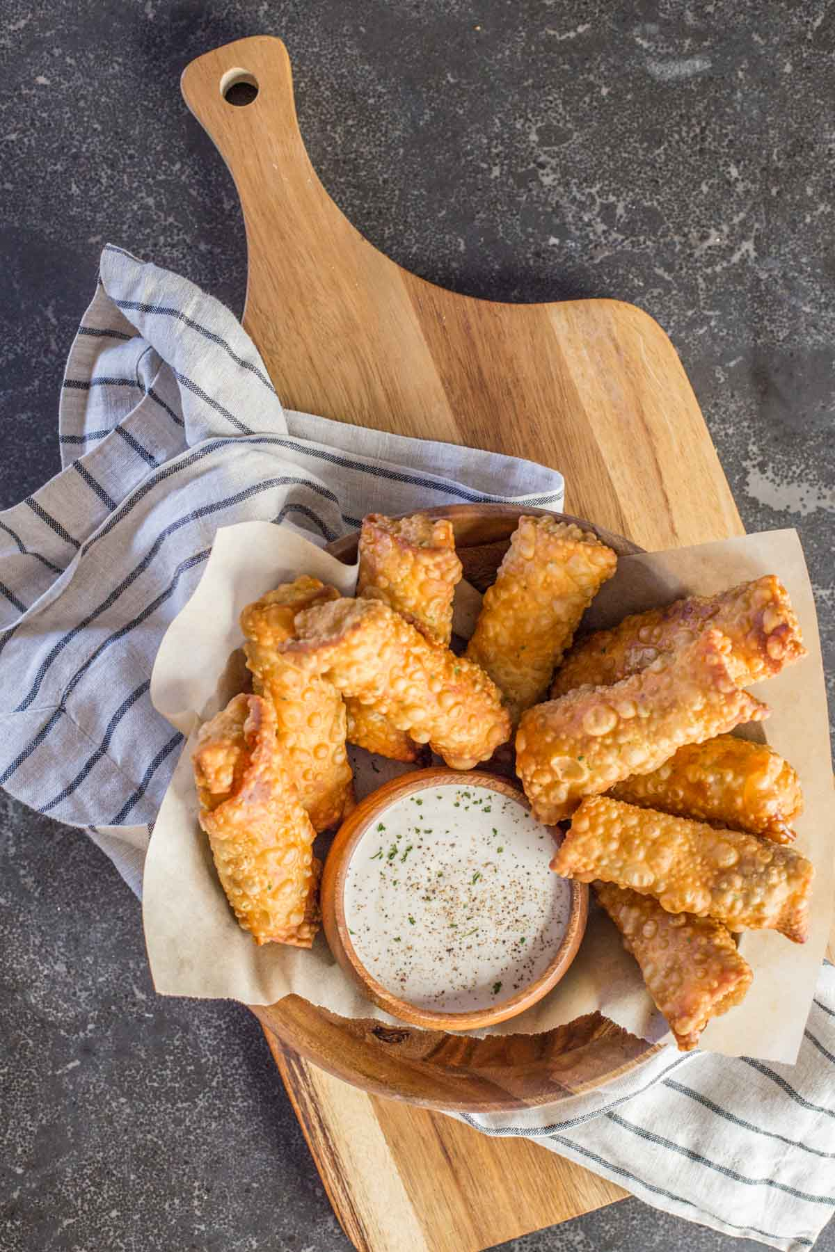Fried Sloppy Joe Rolls in a wood bowl, along with a small wood bowl of ranch dip.