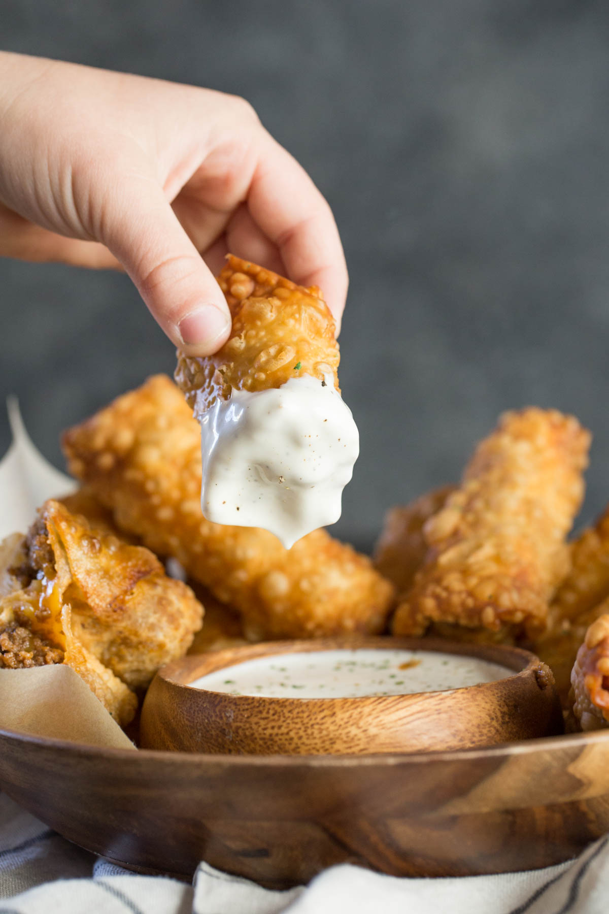 A half of a Fried Sloppy Joe Roll that has been dipped into a small bowl of ranch dip, that is surrounded by more Fried Sloppy Joe Rolls.