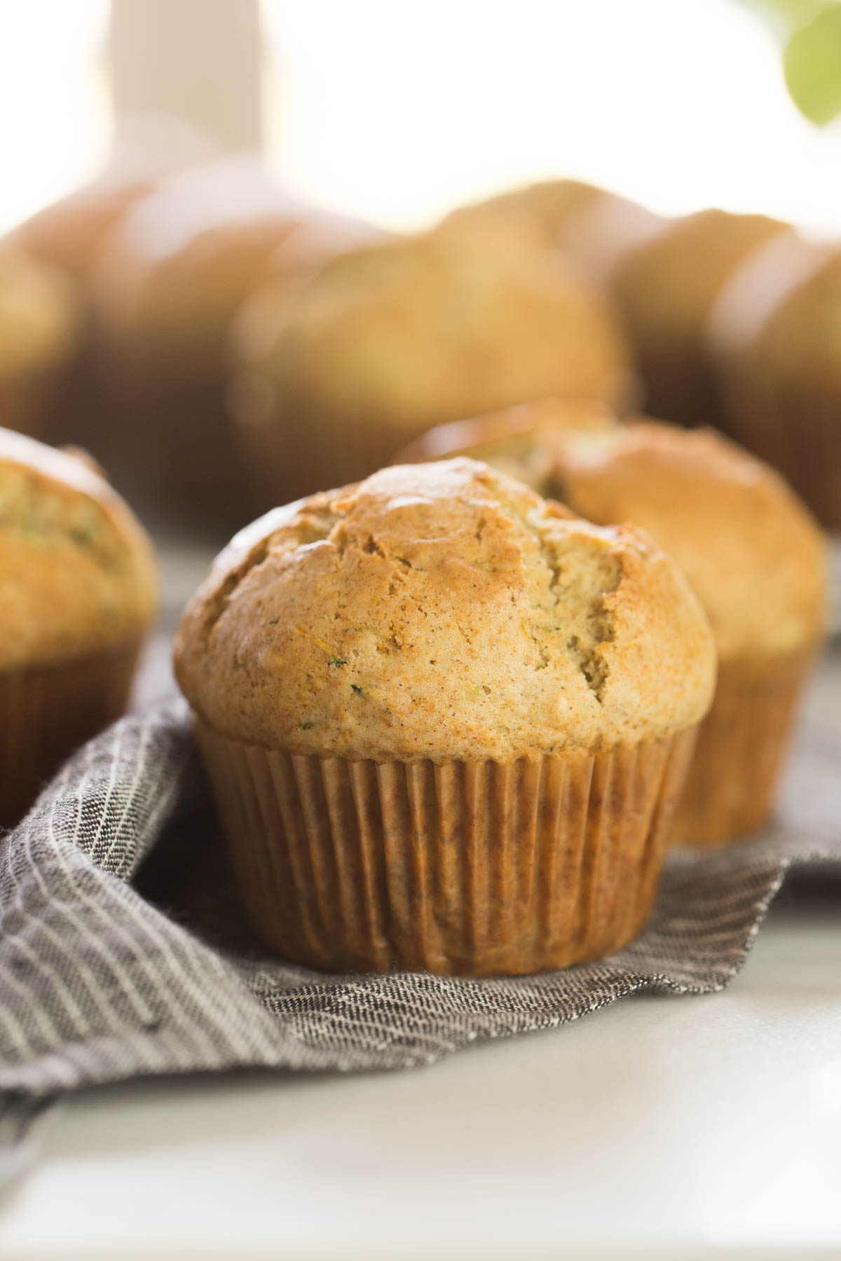 Three Healthier Zucchini Muffins on a cloth napkin, with more muffins in the background.