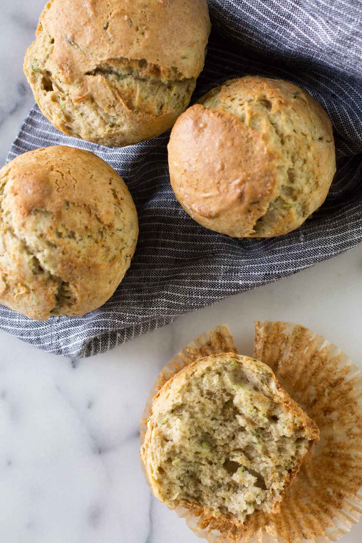 A half of a Healthier Zucchini Muffin sitting on its wrapper, with three more whole muffins sitting on a cloth napkin.