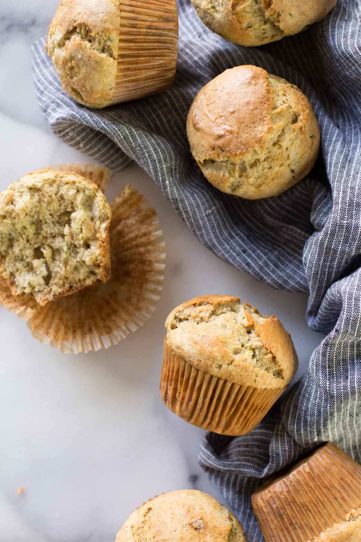 A half of a Healthier Zucchini Muffin sitting on its wrapper, with more whole muffins around it.